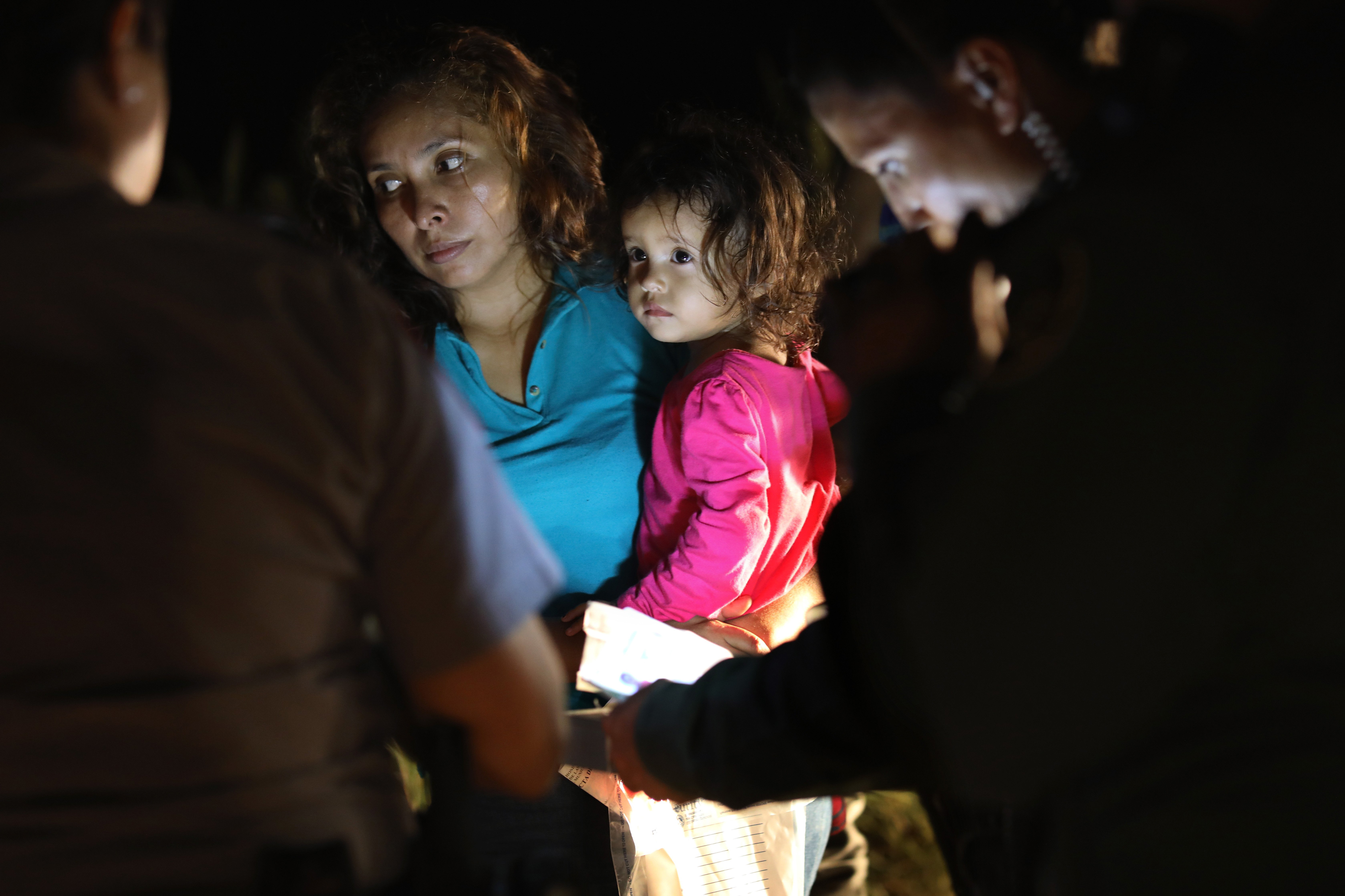 A Honduran mother holds her two-year-old as U.S. Border Patrol as agents review their papers near the U.S.-Mexico border in McAllen, Texas on June 12, 2018. The asylum seekers had rafted across the Rio Grande from Mexico and were detained by U.S. Border Patrol agents before being sent to a processing center for possible separation.