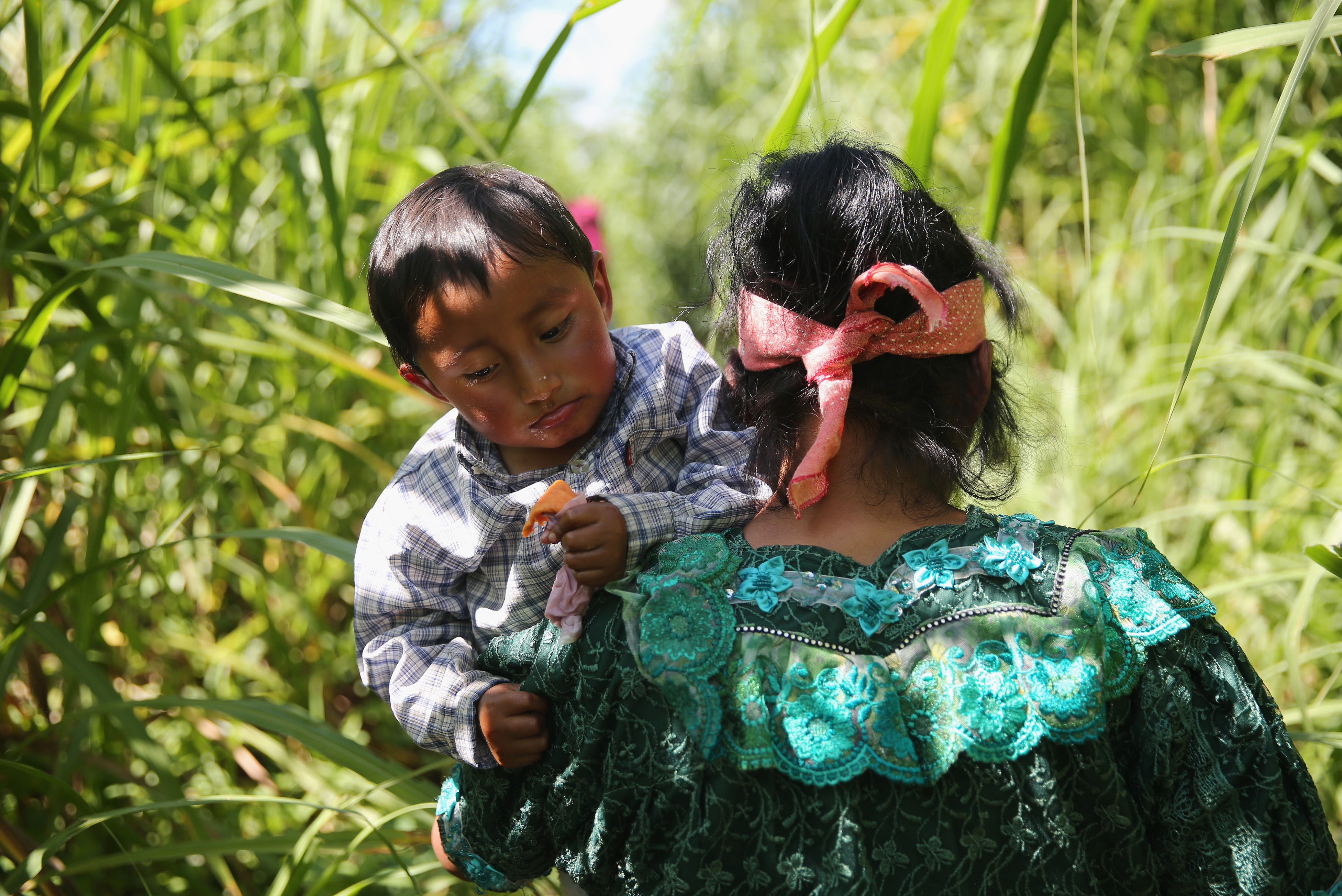 An Indigenous family walks from Guatemala into Mexico after illegally crossing the border at the Suchiate River in Talisman, Mexico on Aug. 1, 2013.