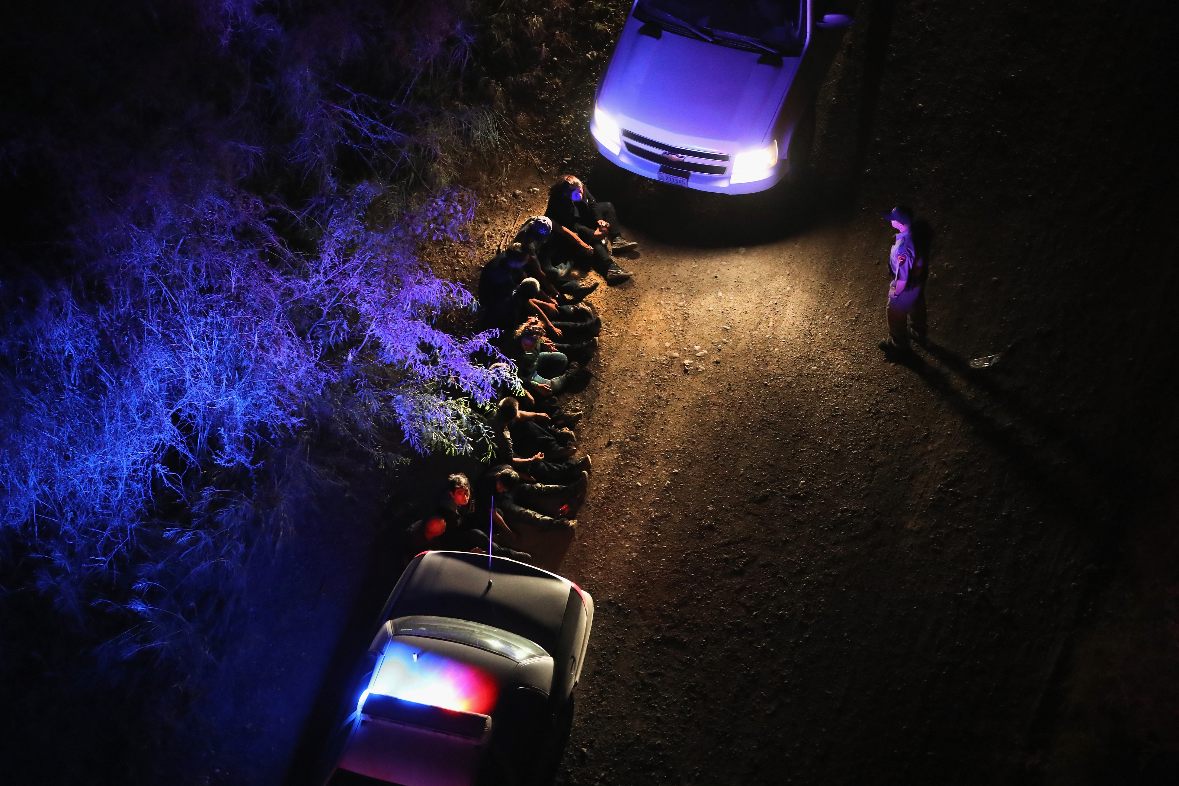 U.S. Border Patrol agents take undocumented immigrants into custody after capturing them after they crossed Rio Grande from Mexico into Texas near Sullivan City, Texas on Aug. 18, 2016.