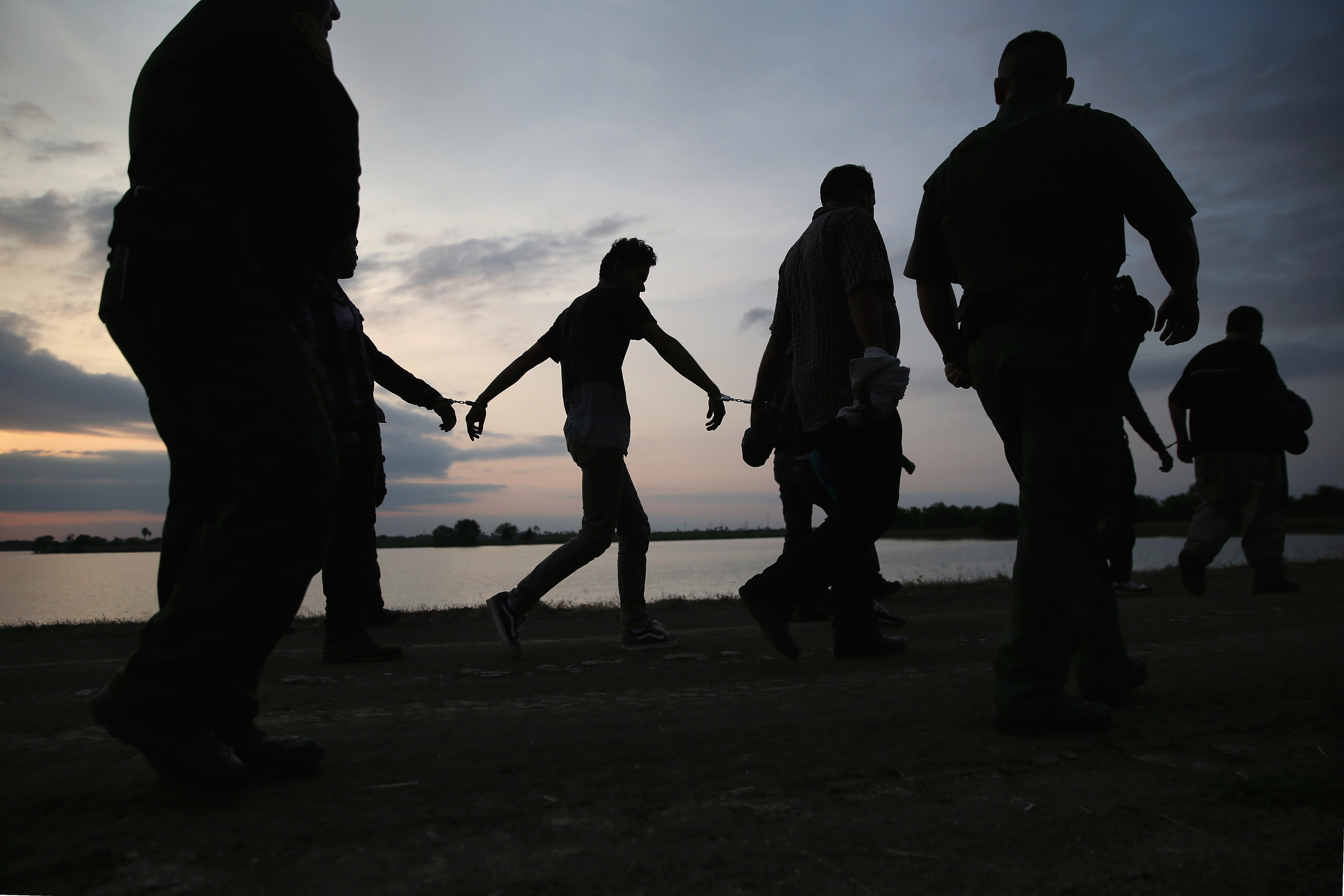 Undocumented immigrants are led after being caught and handcuffed by Border Patrol agents near the U.S.-Mexico border in Weslaco, Texas on April 13, 2016.