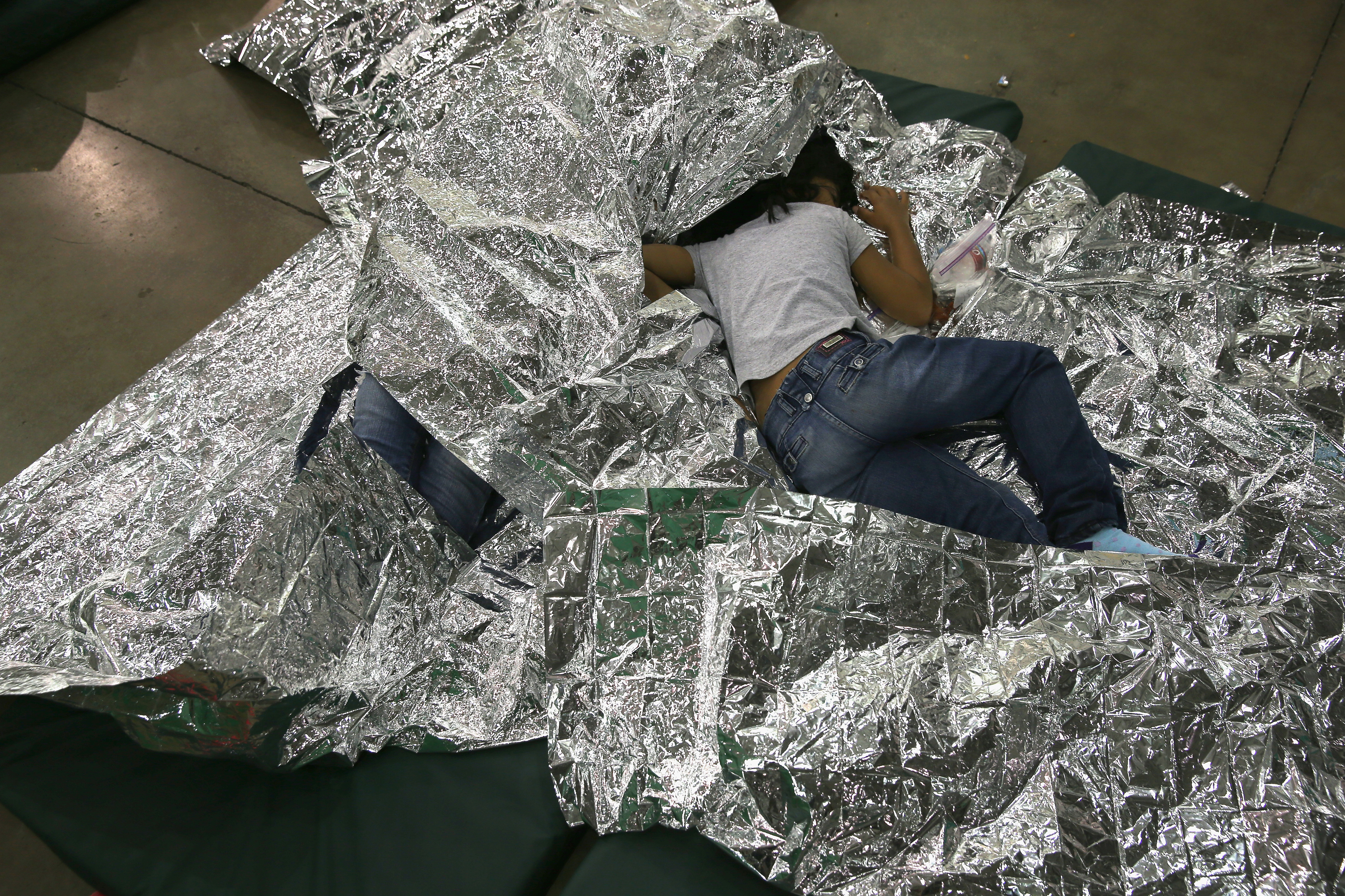 A girl from Central America rests on thermal blankets at a detention facility run by the U.S. Border Patro in McAllen, Texasl on Sept. 8, 2014.