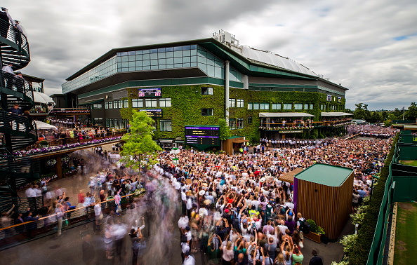 Crowds gather outside centre court on day thirteen of the Wimbledon Championships at the All England Lawn Tennis and Croquet Club, Wimbledon.