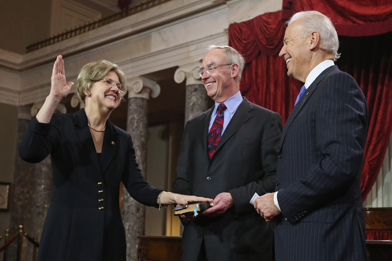 U.S. Sen. Elizabeth Warren (D-MA) (L) participates in a reenacted swearing-in with her husband Bruce Mann and U.S. Vice President Joe Biden in the Old Senate Chamber at the U.S. Capitol  January 3, 2013 in Washington, D.C.