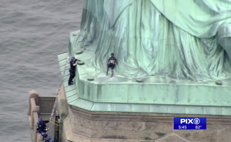In this image made from video by PIX11, a woman leans against the robes of the Statue of Liberty on Liberty Island, in New York, July 4, 2018.