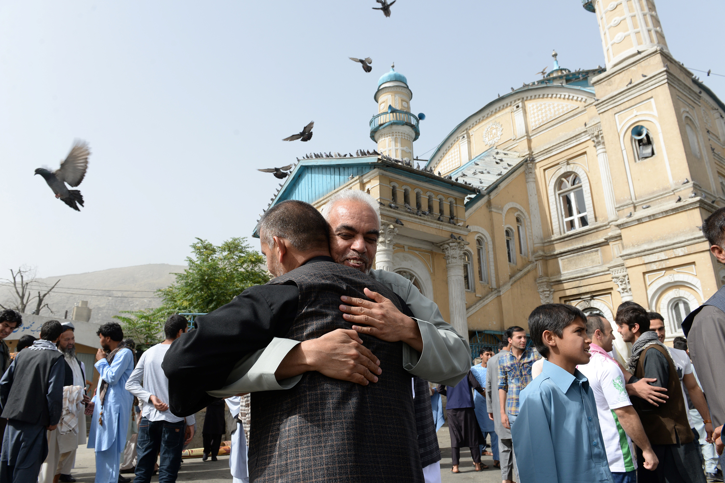 Afghan Muslims hug each other after offering prayers at the start of the Eid al-Fitr holiday which marks the end of Ramadan at the Shah-e Do Shamshira mosque in Kabul on June 15, 2018.