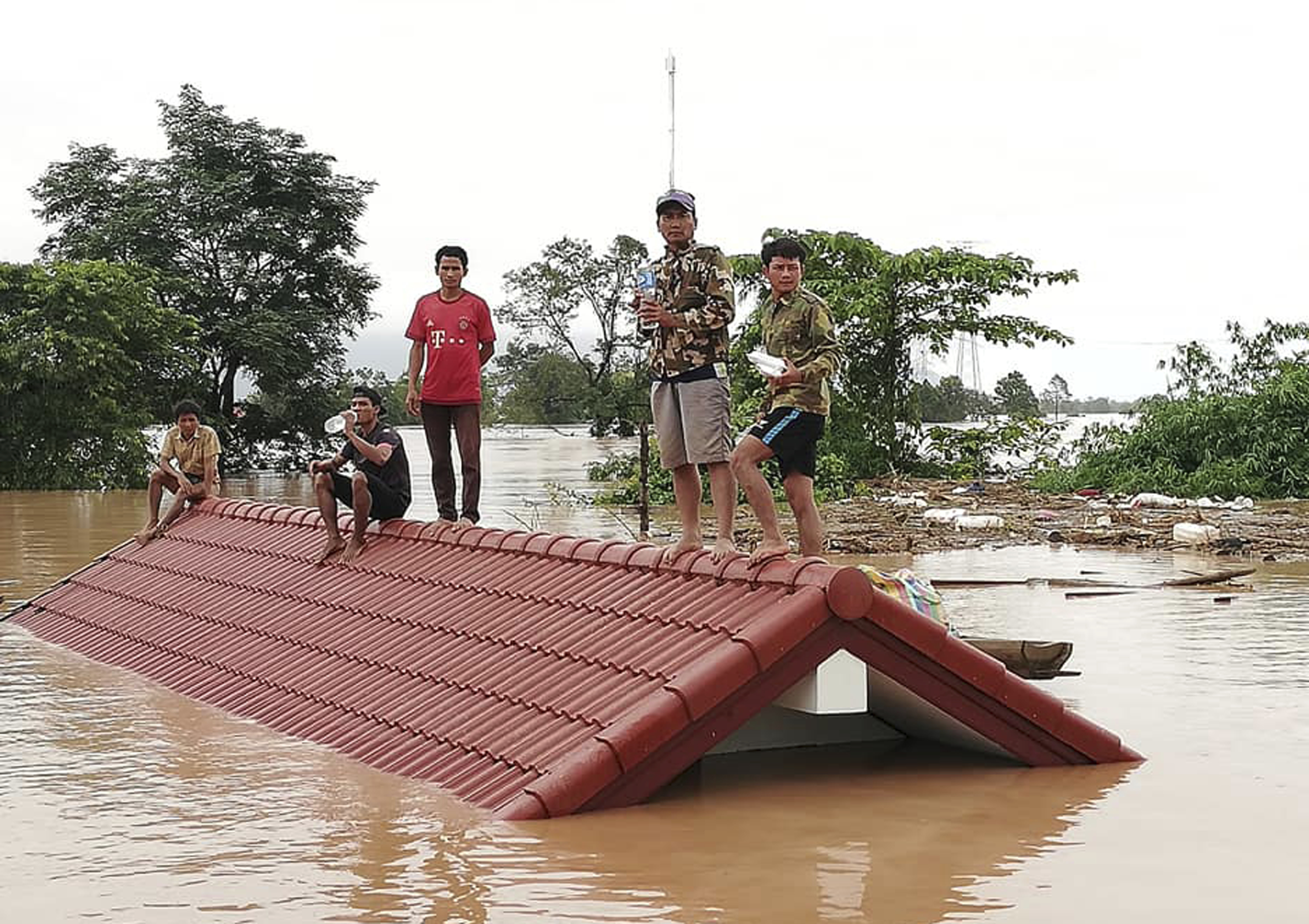 Villagers take refuge on a rooftop above flood waters from a collapsed dam in the Attapeu district of southern Laos, on July 24, 2018.