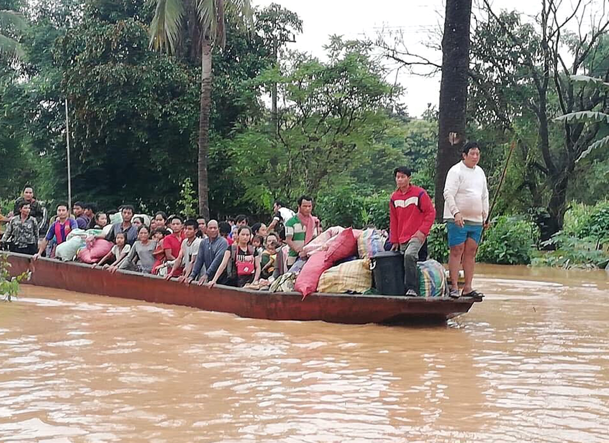 People are evacuated by boat after a dam failed in southeastern Laos.
