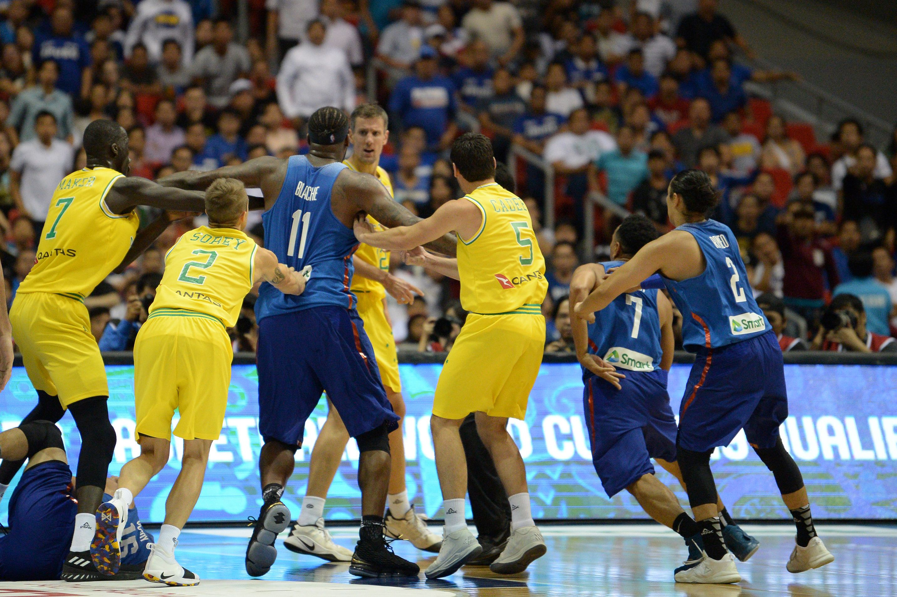 Philippine (blue) and Australian (yellow) players engage in a brawl during their FIBA World Cup Asian qualifier game at the Philippine arena in Bocaue town, Bulacan province, north of Manila on July 2, 2018. - Australia won by default 89-53.