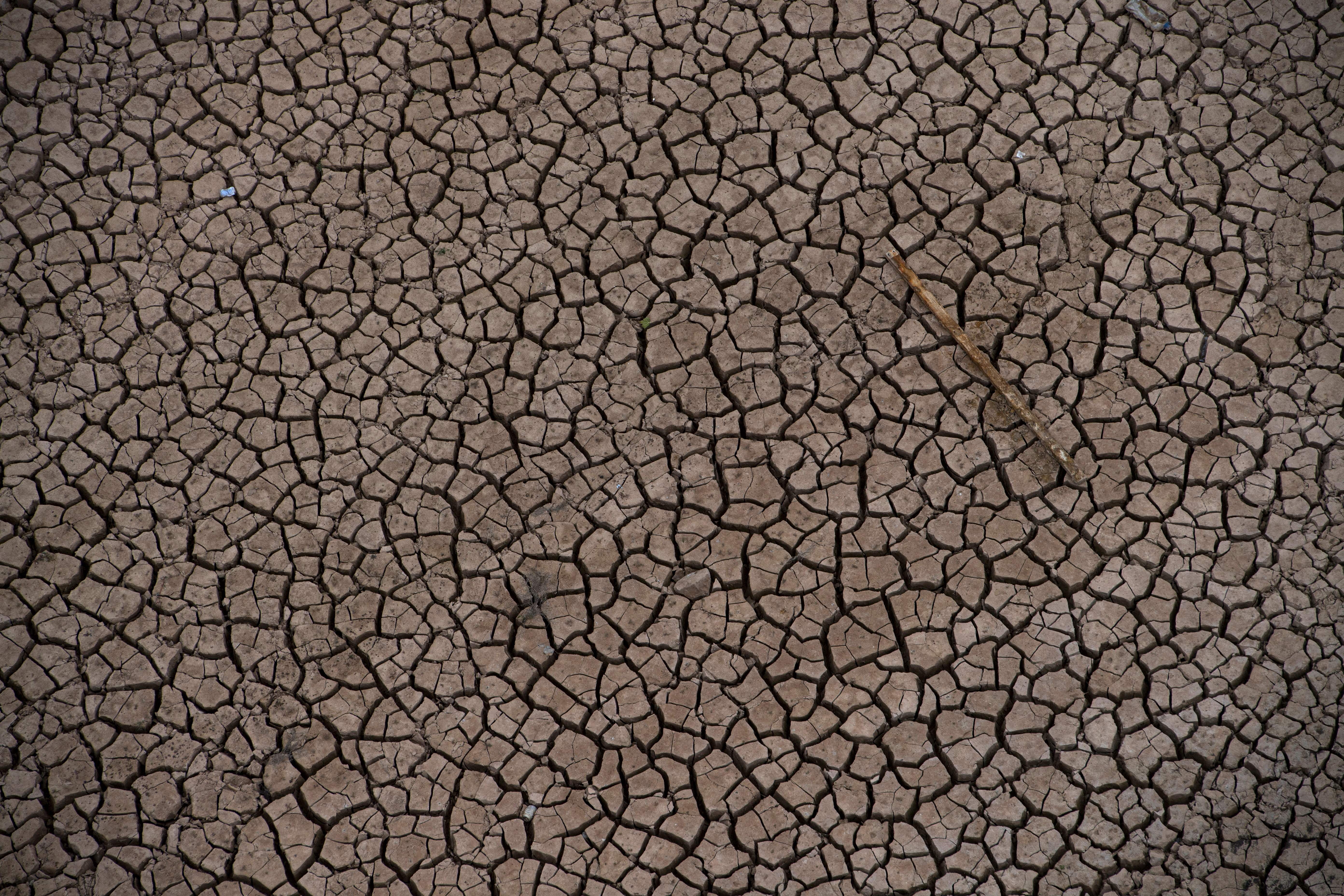 A picture shows cracked earth amid low water levels at a reservoir in drought-stricken Entrepenas near Sacedon on November 24, 2017.