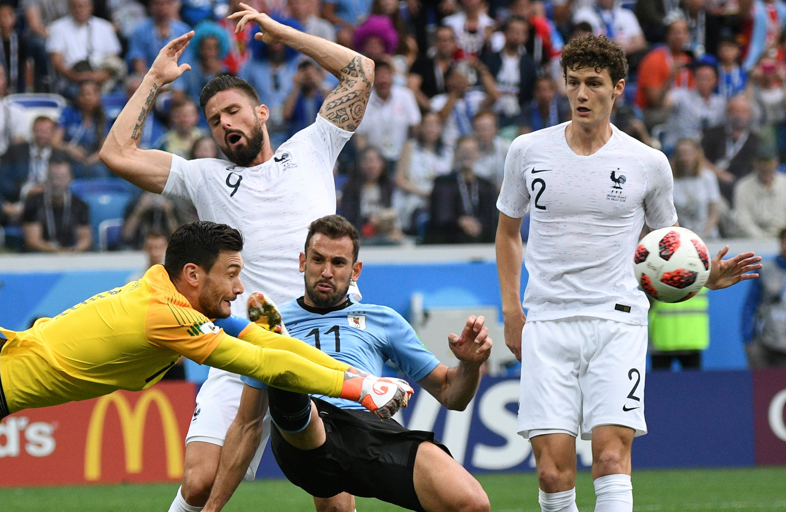 France's goalkeeper Hugo Lloris, left, makes a save during the quarterfinal soccer game between Uruguay and France on July 6, 2018.