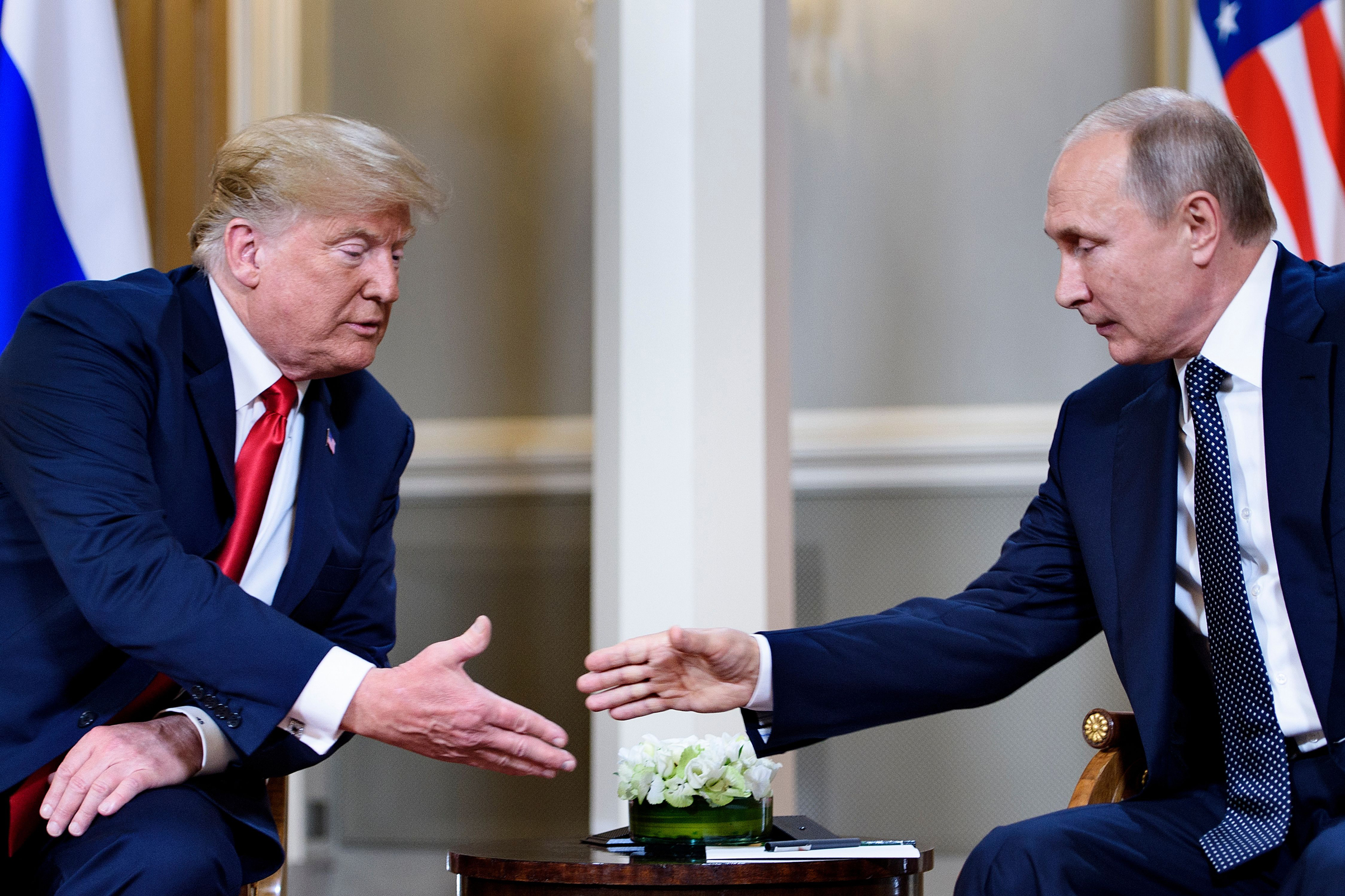 U.S. President Donald Trump (left) and Russian President Vladimir Putin reach to shake hands before a meeting in Helsinki, on July 16, 2018.