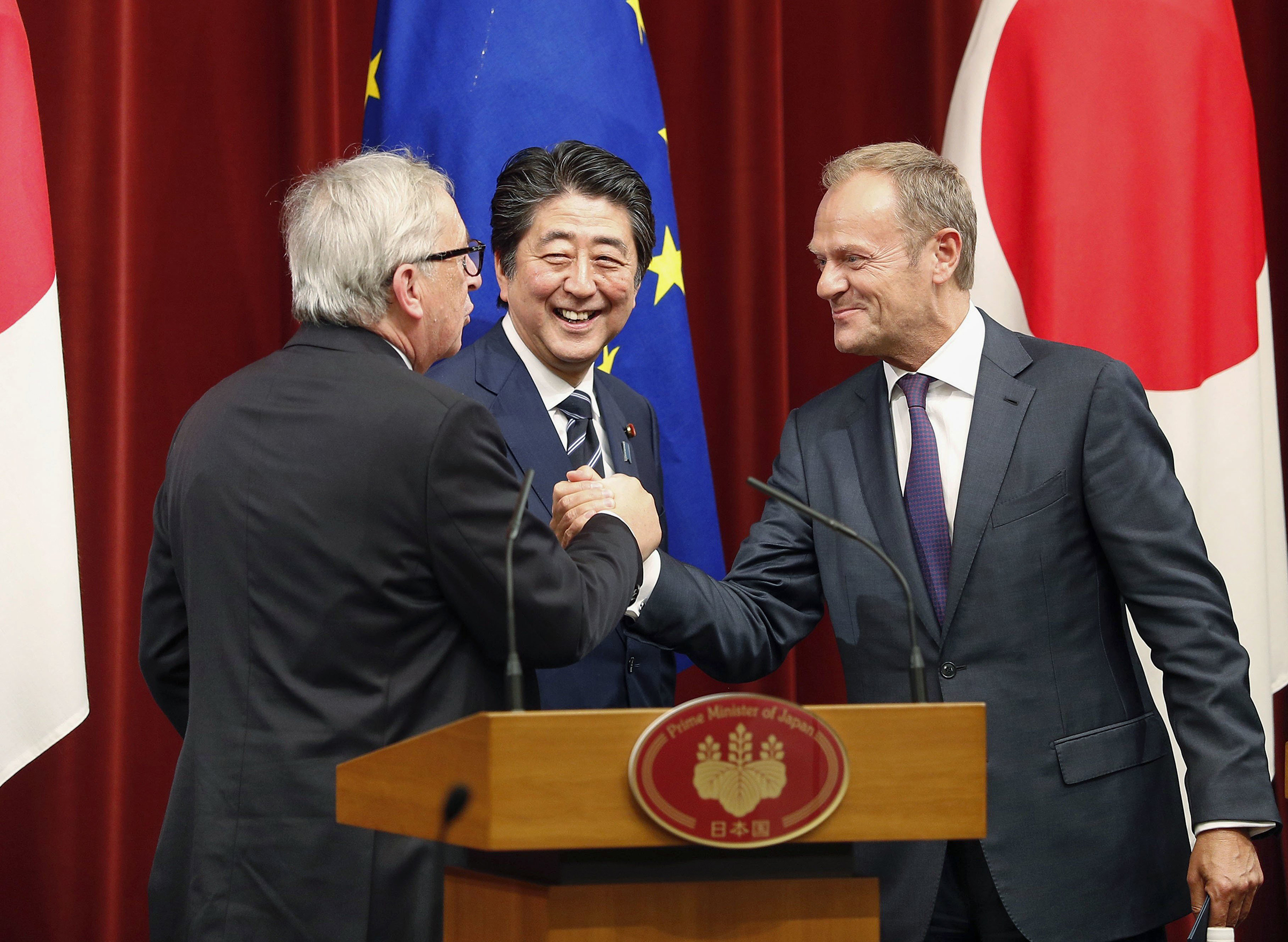 European Council President Donald Tusk (R) and European Commission President Jean-Claude Juncker (L), alongside Japanese Prime Minister Shinzo Abe, shake hands at Abe's office in Tokyo on July 17, 2018, after they signed a free trade deal with Japan.