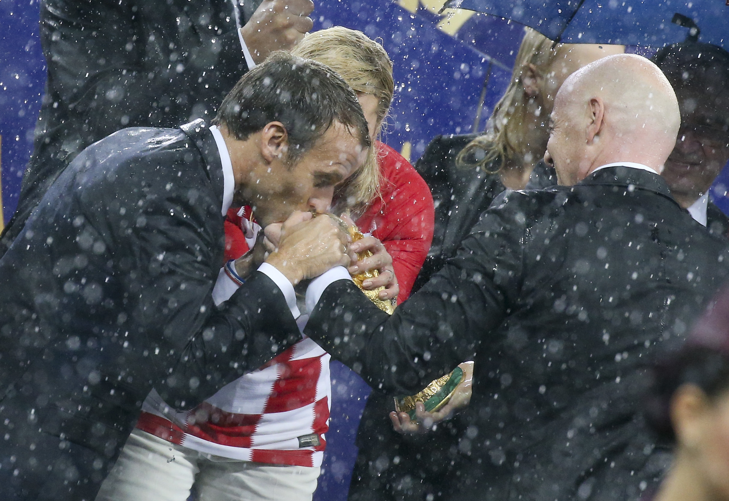 President of France Emmanuel Macron and President of Croatia Kolinda Grabar-Kitarovic want to kiss the World Cup held by FIFA President Gianni Infantino during the trophy ceremony following the 2018 FIFA World Cup Russia Final between France and Croatia at Luzhniki Stadium on July 15, 2018 in Moscow, Russia. (Photo by Jean Catuffe/Getty Images)