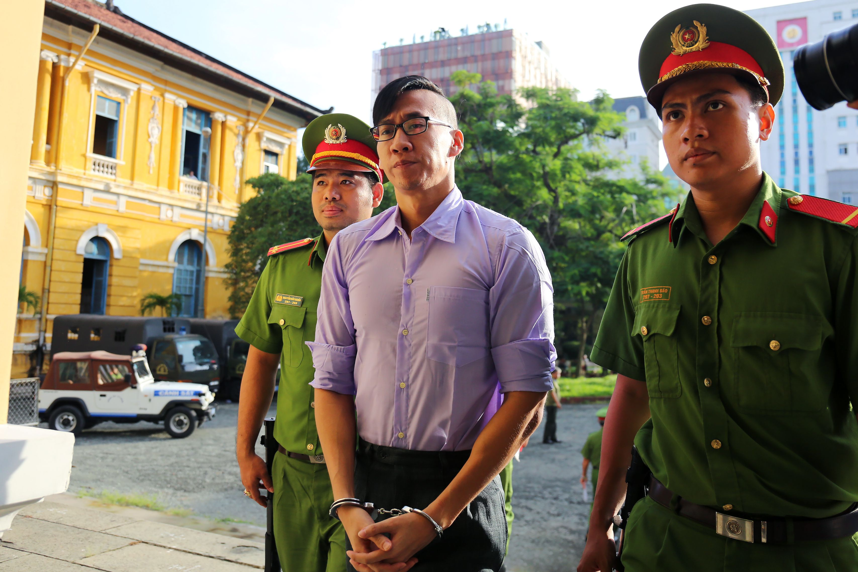American-Vietnamese citizen William Nguyen is escorted by policemen to a courtroom for his trial in Ho Chi Minh City on July 20, 2018.