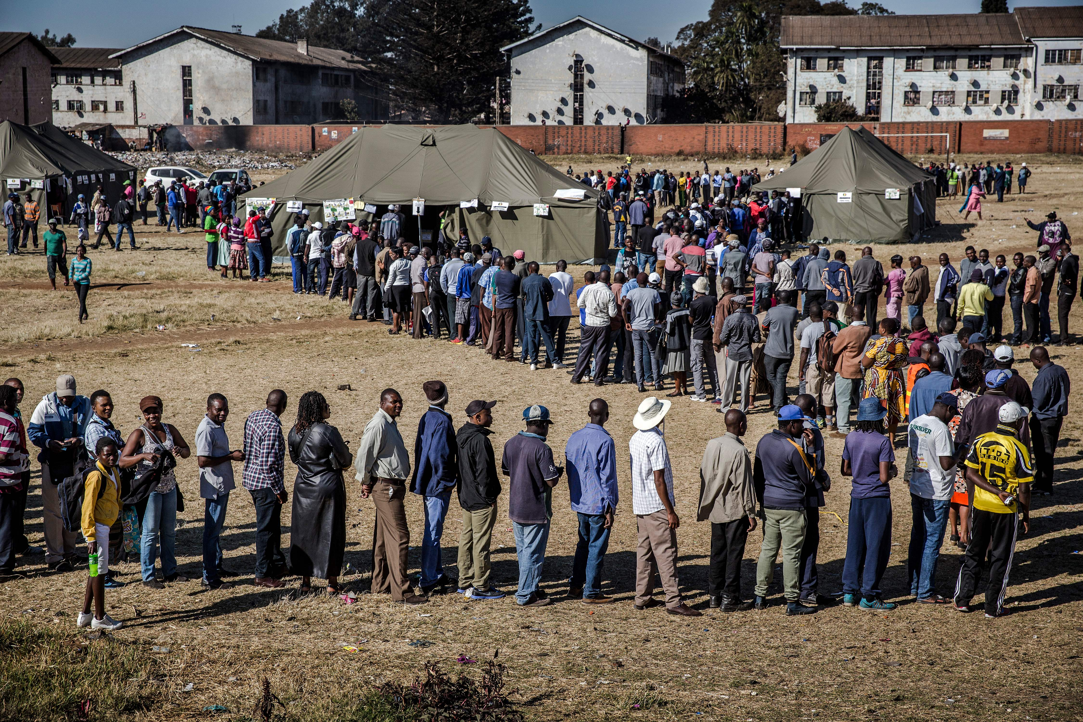People queue in order to cast their ballot outside a polling station located in the suburb of Mbare in Zimbabwe's capital Harare, on July 30, 2018.