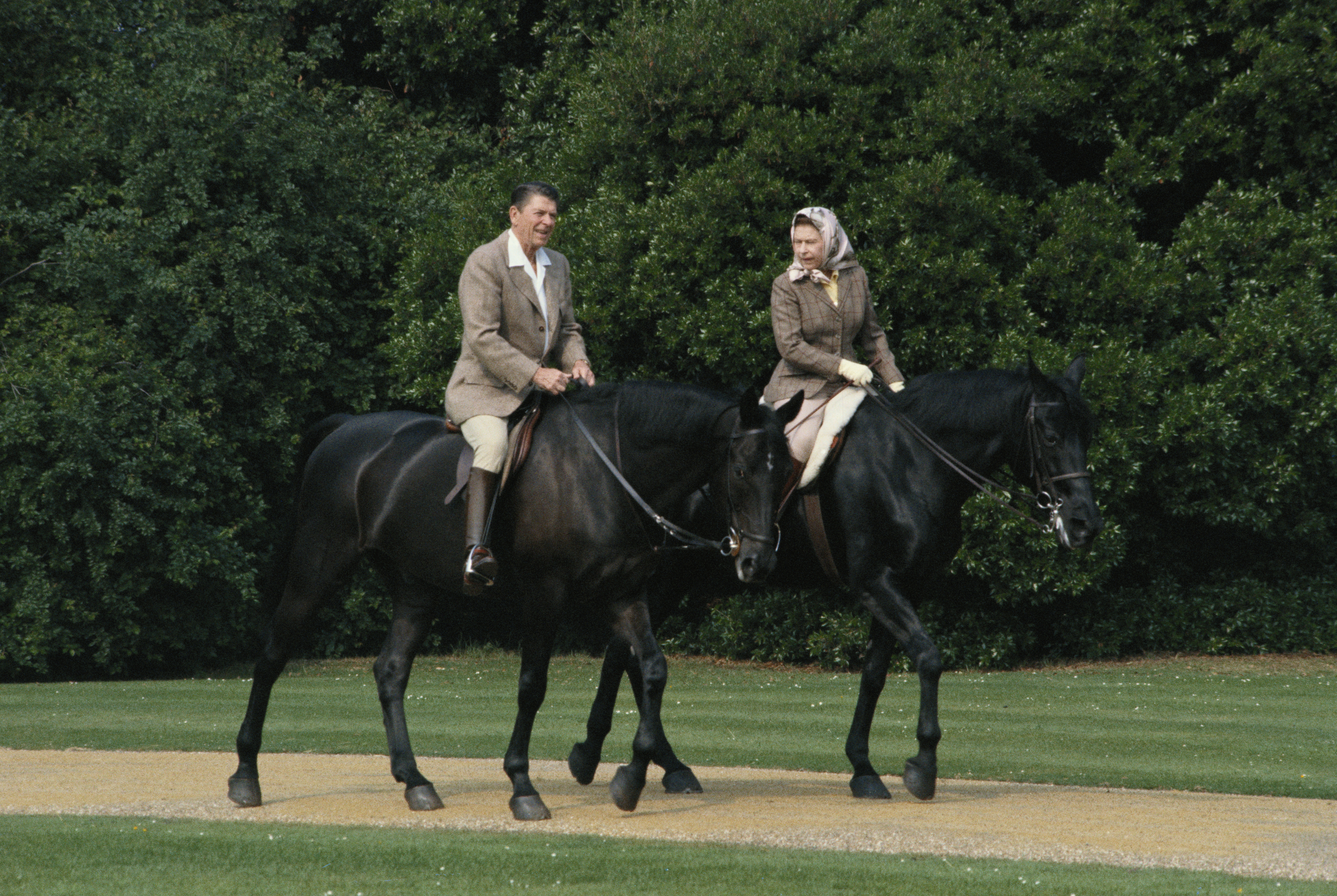 Queen Elizabeth II riding in the grounds of Windsor Castle with US President Ronald Reagan, during his state visit to the UK, 8th June 1982.