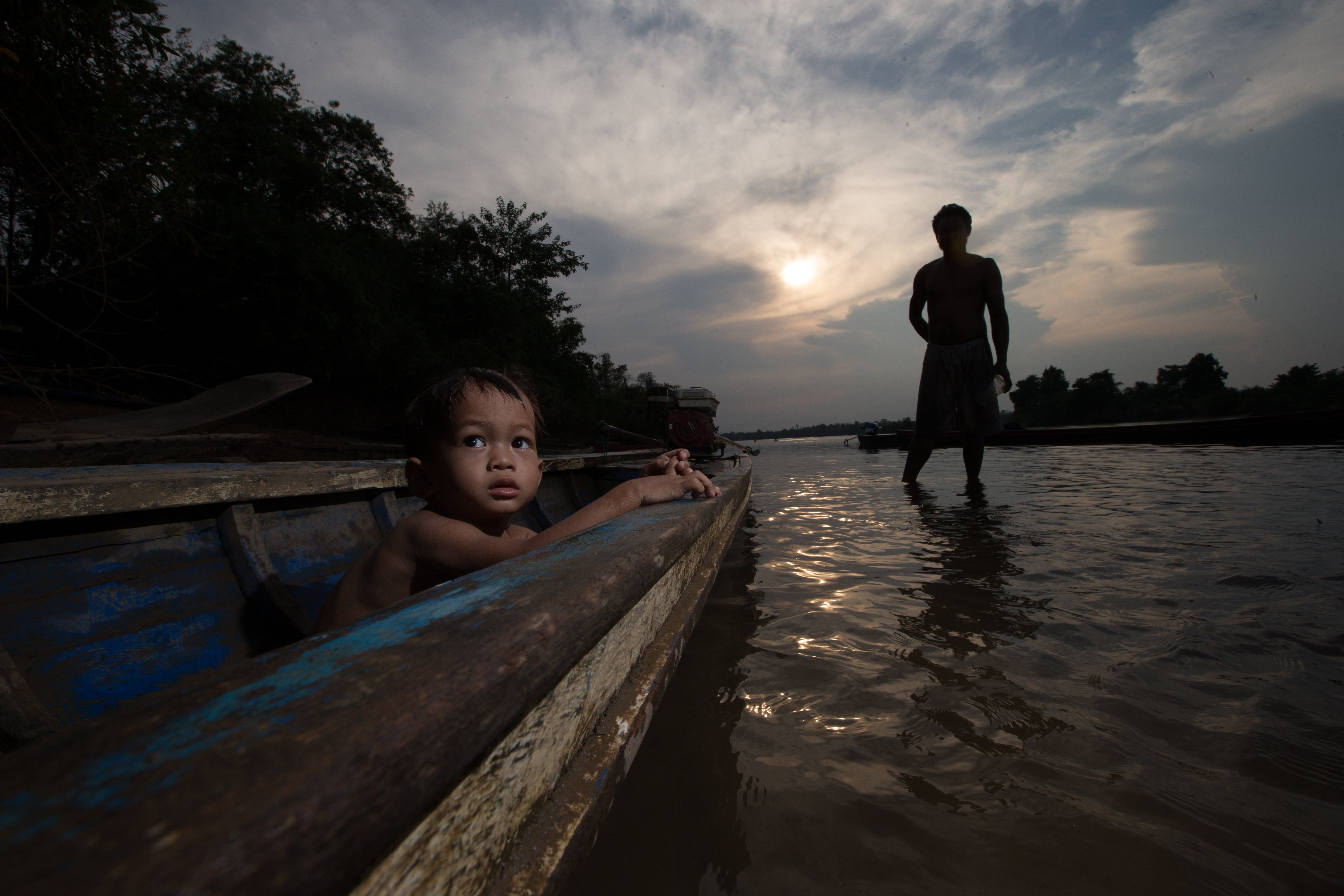 A boy sits in a boat near his father in Stung Treng, Cambodia.
