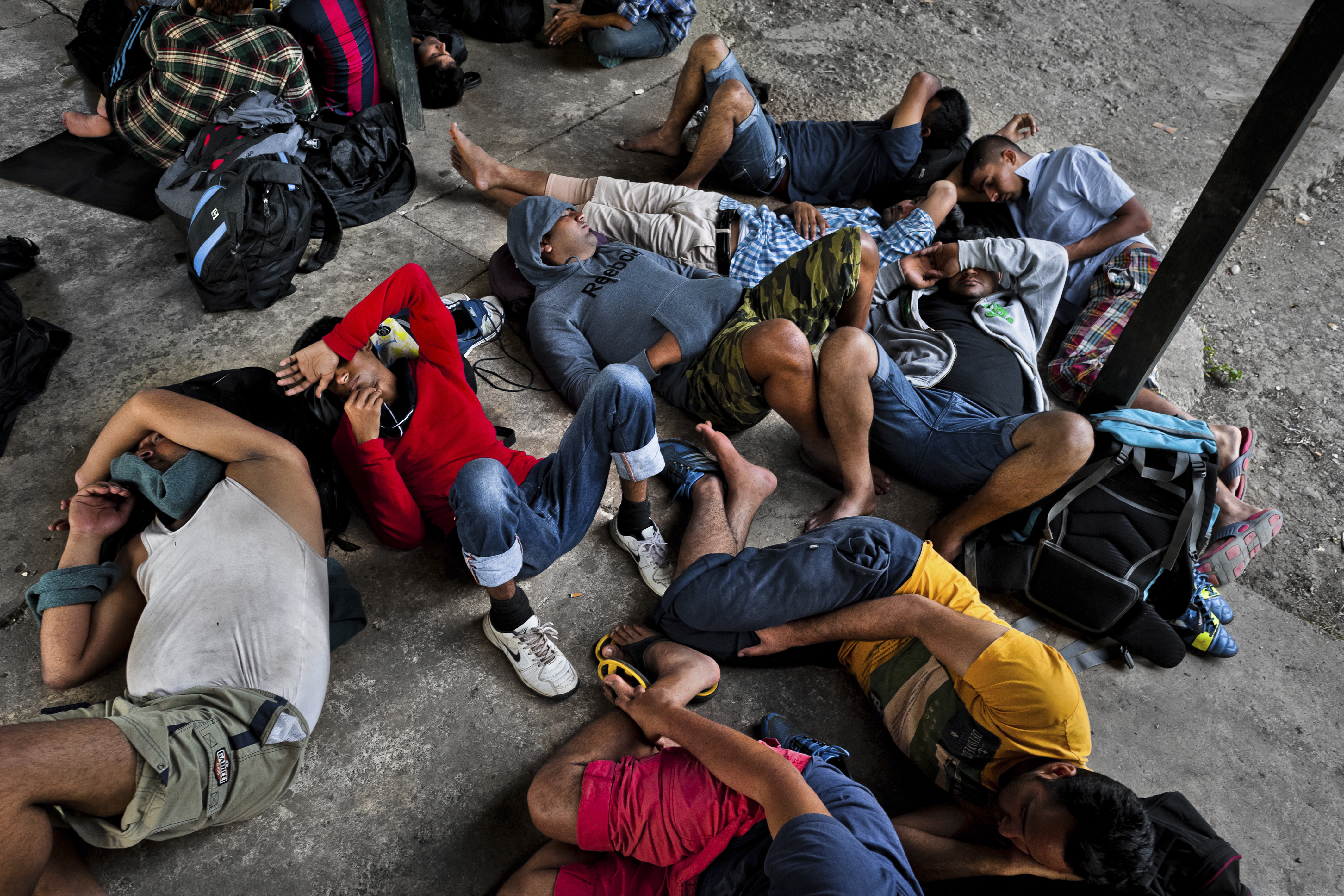 Nepalese immigrants, heading to the southern U.S. border, lie exhausted on the ground in the border checkpoint after crossing the jungle of Darién gap on January 28, 2015 in Darien, Panama.