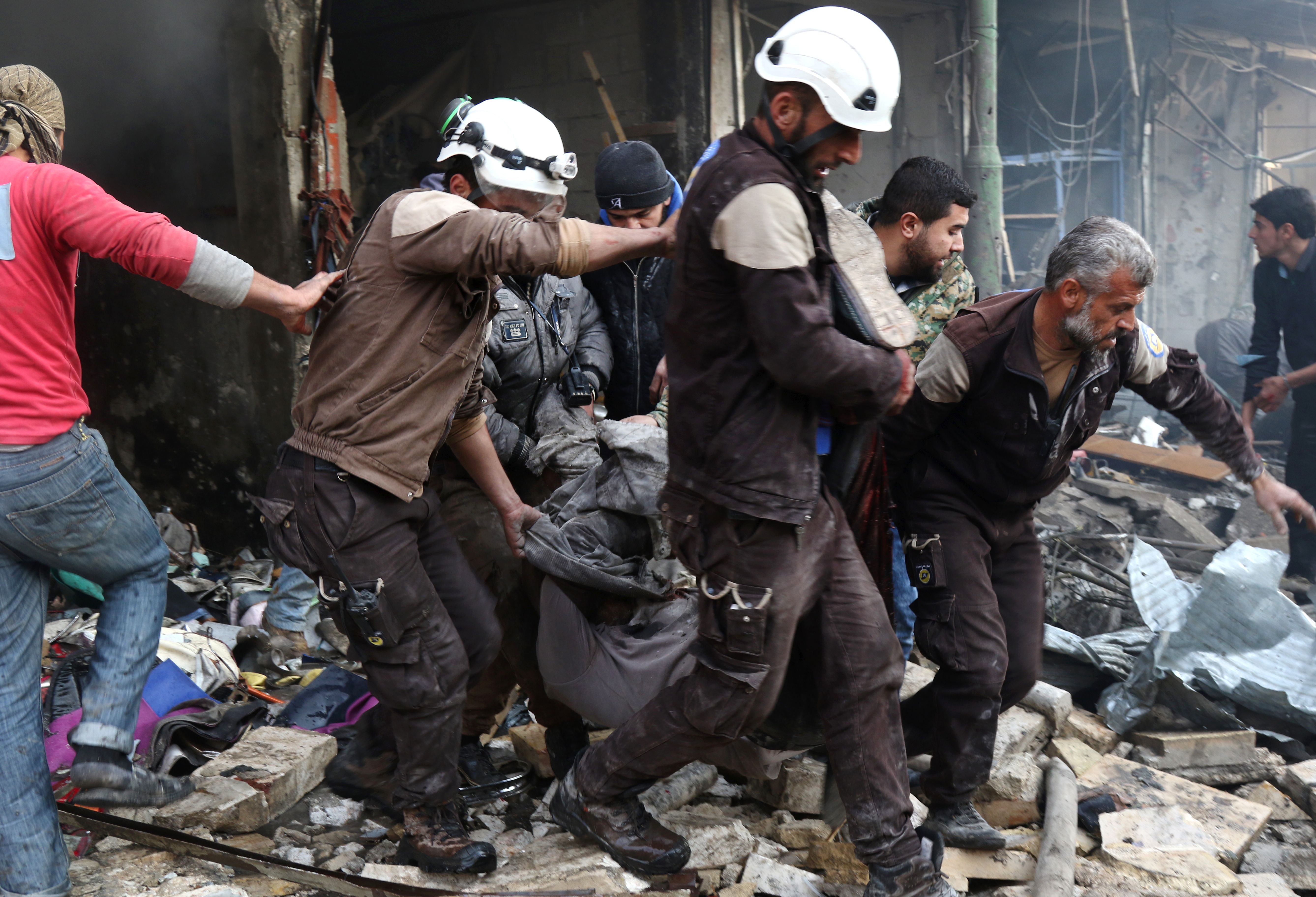 Syrian Civil Defence volunteers, also known as the White Helmets, evacuate a victim from a building following an air strike on the village of Maaret al-Numan, in the country's northern province of Idlib, on Dec. 4, 2016.