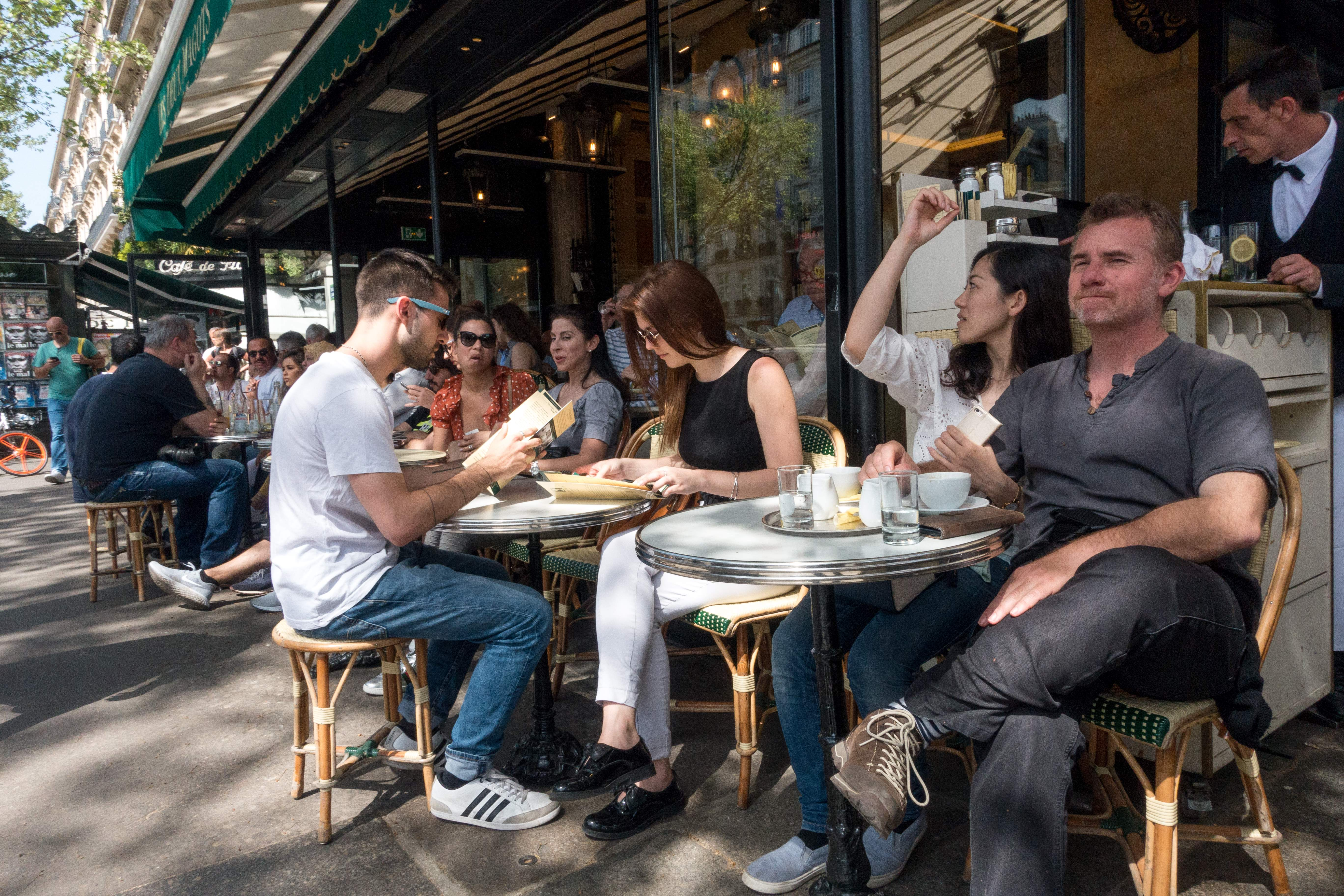 People enjoy the sun and warm spring temperatures at the terrace of the French cafe  Les deux magots  at the Saint-Germain-des-Pres district in Paris, on April 22, 2018.