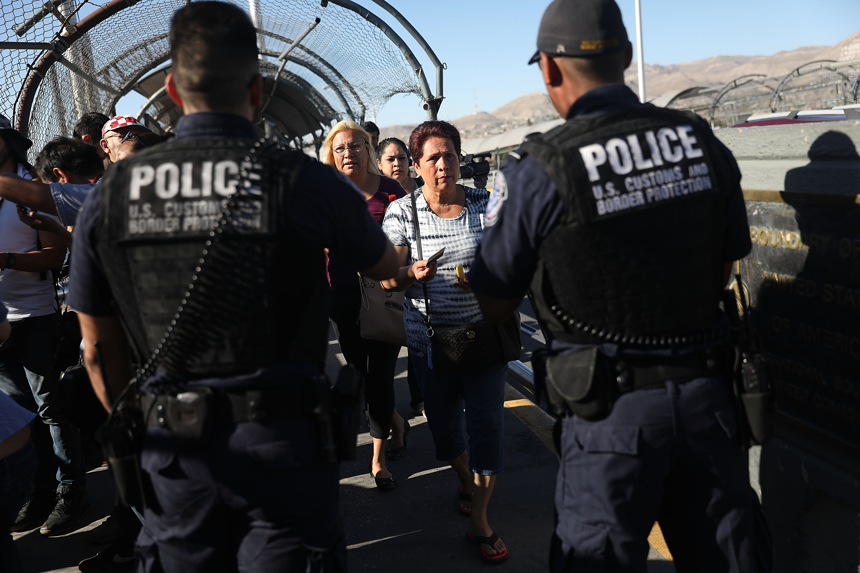 U.S. Border Patrol agents check passports at the Paso Del Norte Port of Entry, where the U.S. and Mexico border meet, as people walk across the bridge to enter the United States on June 20, 2018 in El Paso, Texas.