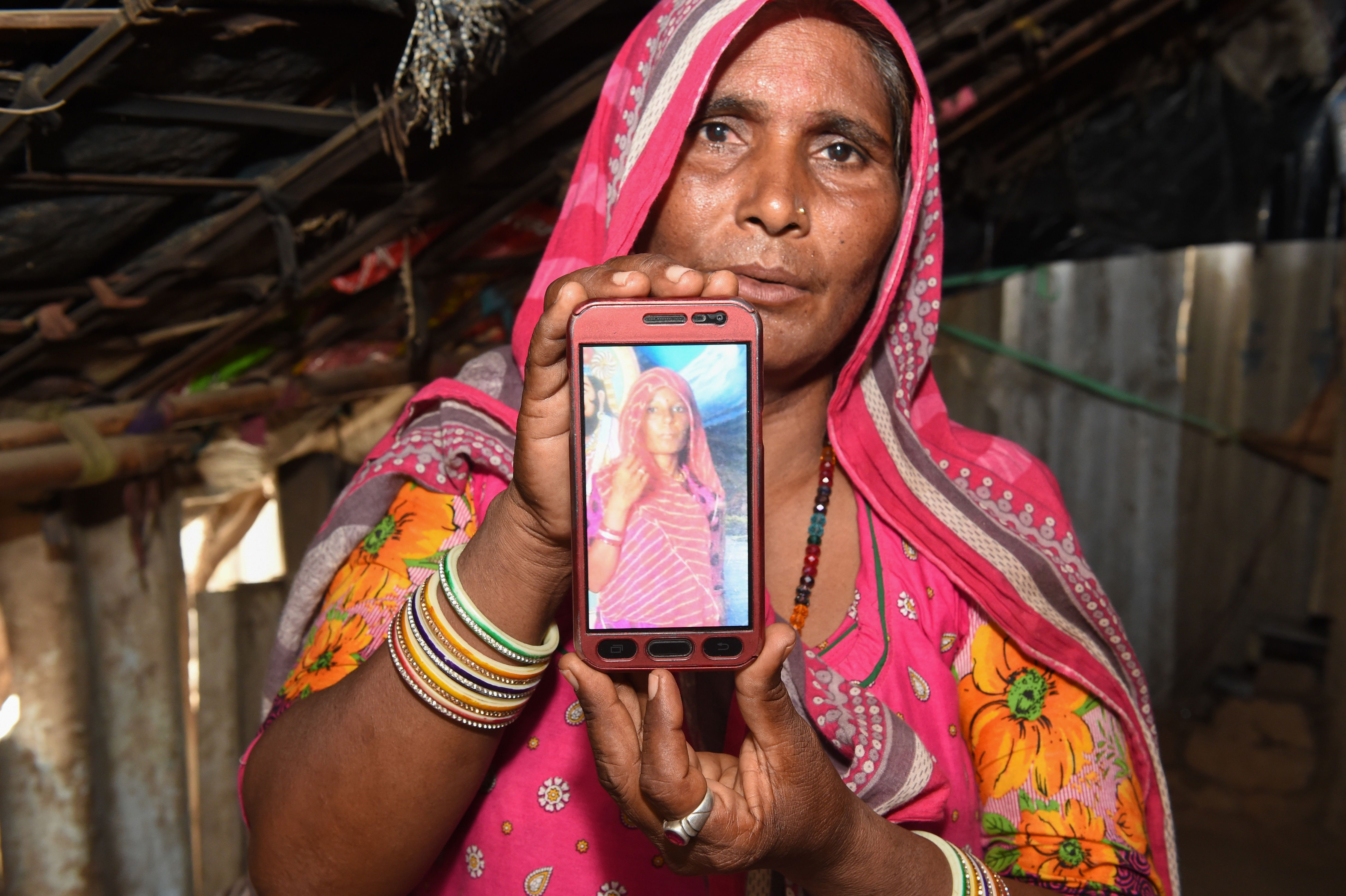 Mohinidevi Nath displays a photo of her cousin Shantadevi Nath, who was killed by a mob that falsely believed she was intent on abducting children, on the outskirts of Ahmedabad in India's Gujarat state on June 27, 2018.