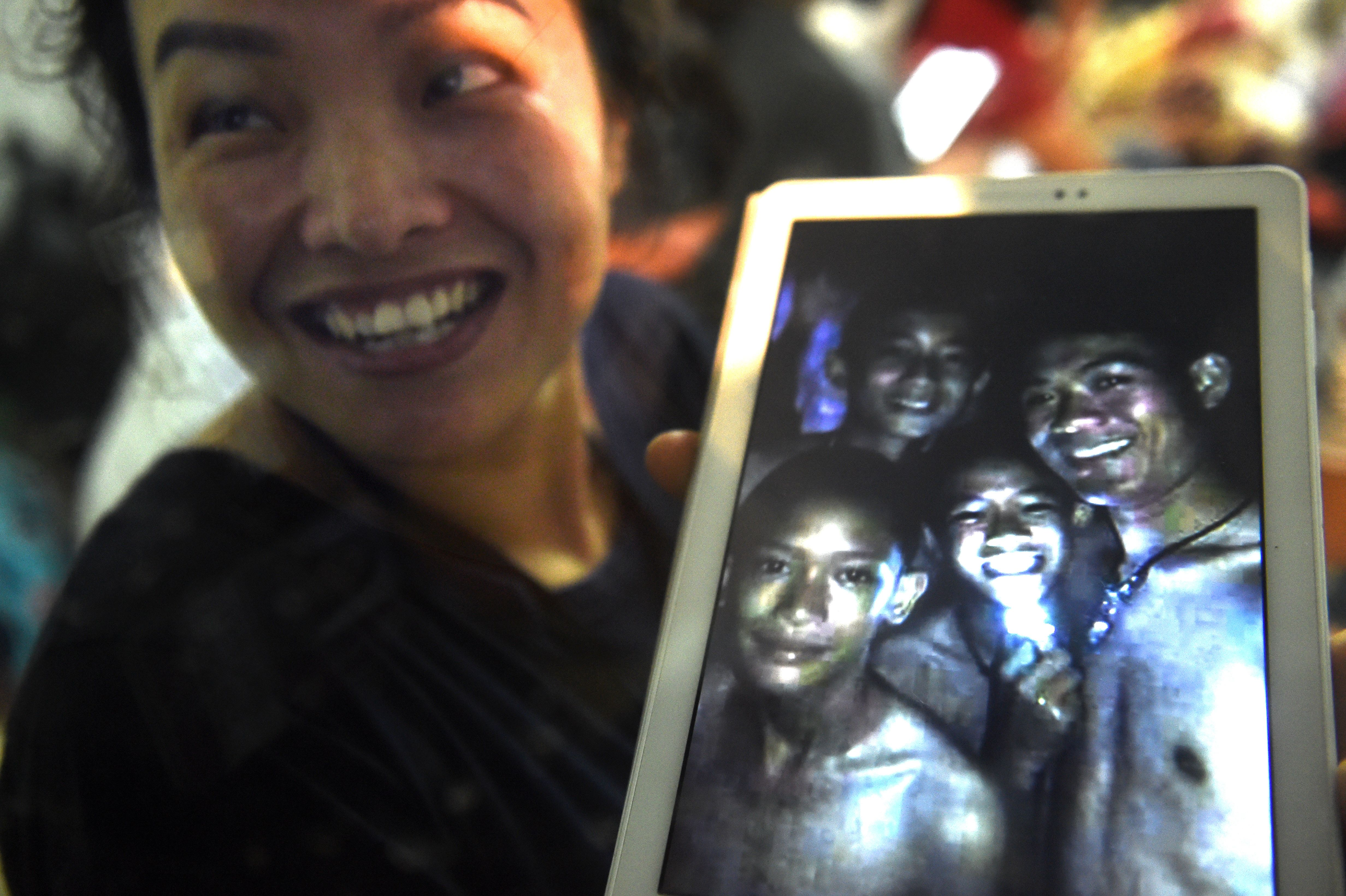 A family member shows a picture of four of the twelve boys trapped in Tham Luang cave at the Khun Nam Nang Non Forest Park in Mae Sai, Thailand on July 2, 2018.