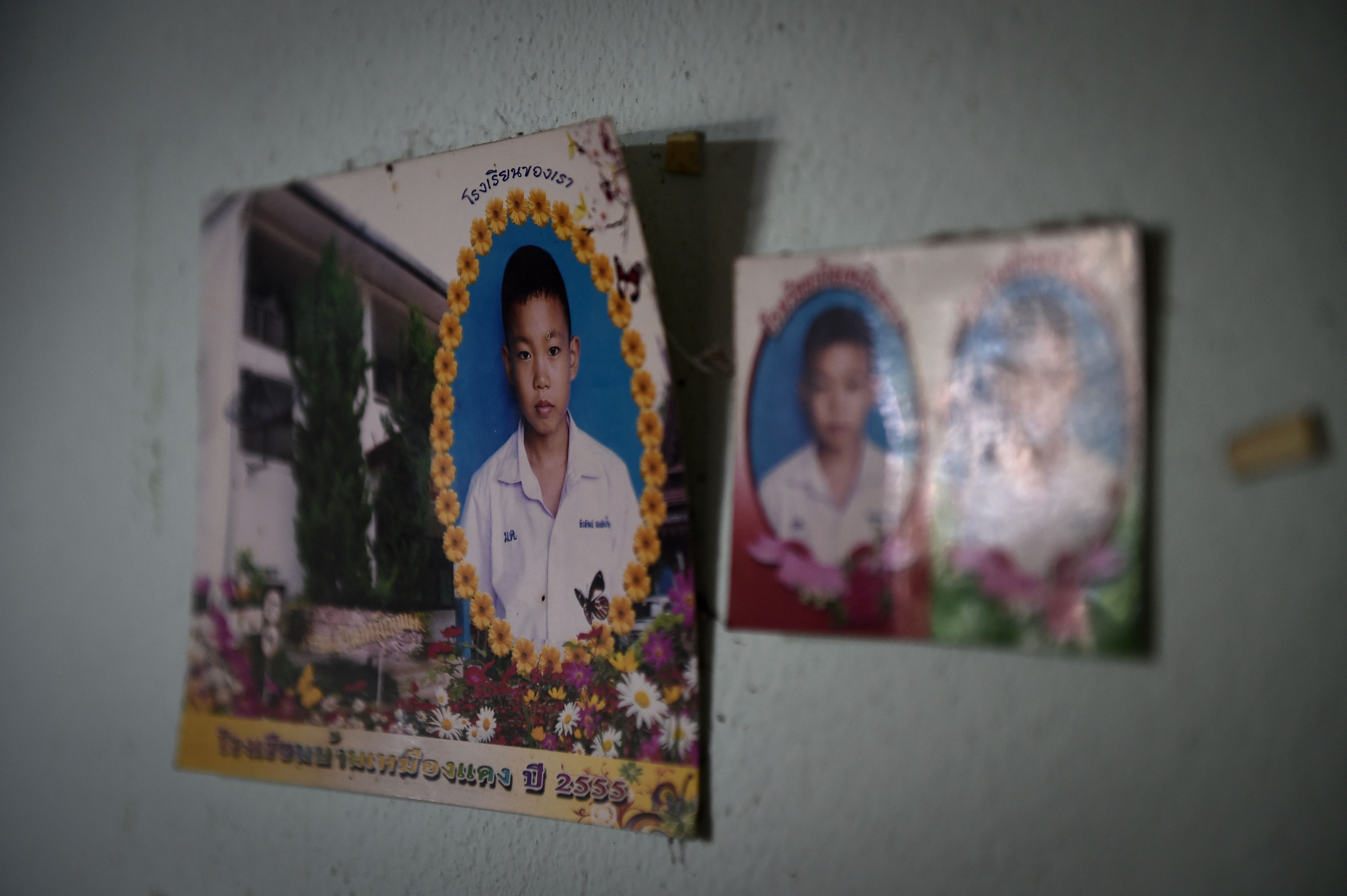 Photographs of Pheeraphat 'Night' Sompiengjai, one of the members of a Thai youth football team currently trapped at the Tham Luang cave, are seen on a wall at his home in Mae Sai on July 4, 2018.