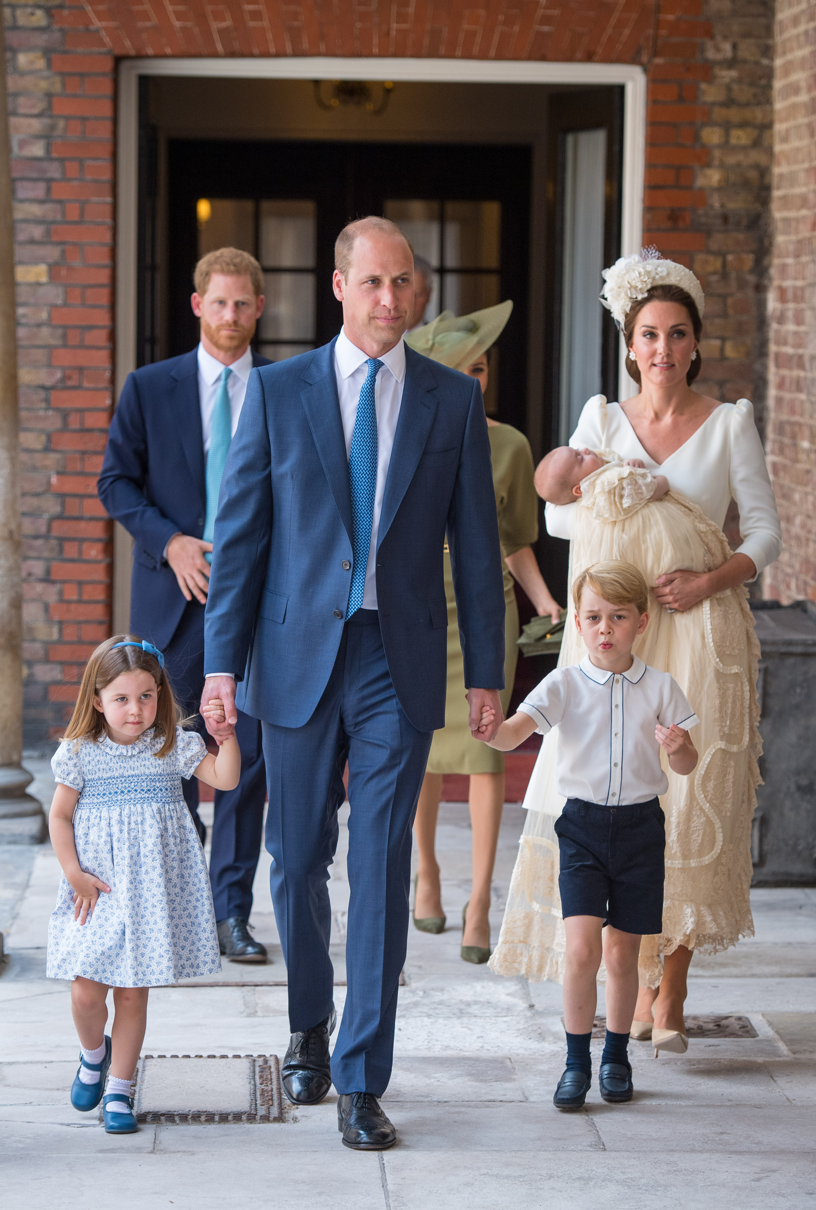 Princess Charlotte and Prince George hold the hands of their father, Prince William, Duke of Cambridge, as they arrive at the Chapel Royal, St James's Palace, London for the christening of their brother, Prince Louis, who is being carried by their mother, Catherine, Duchess of Cambridge on July 09, 2018 in London, England. (Photo by Dominic Lipinski - WPA Pool/Getty Images)