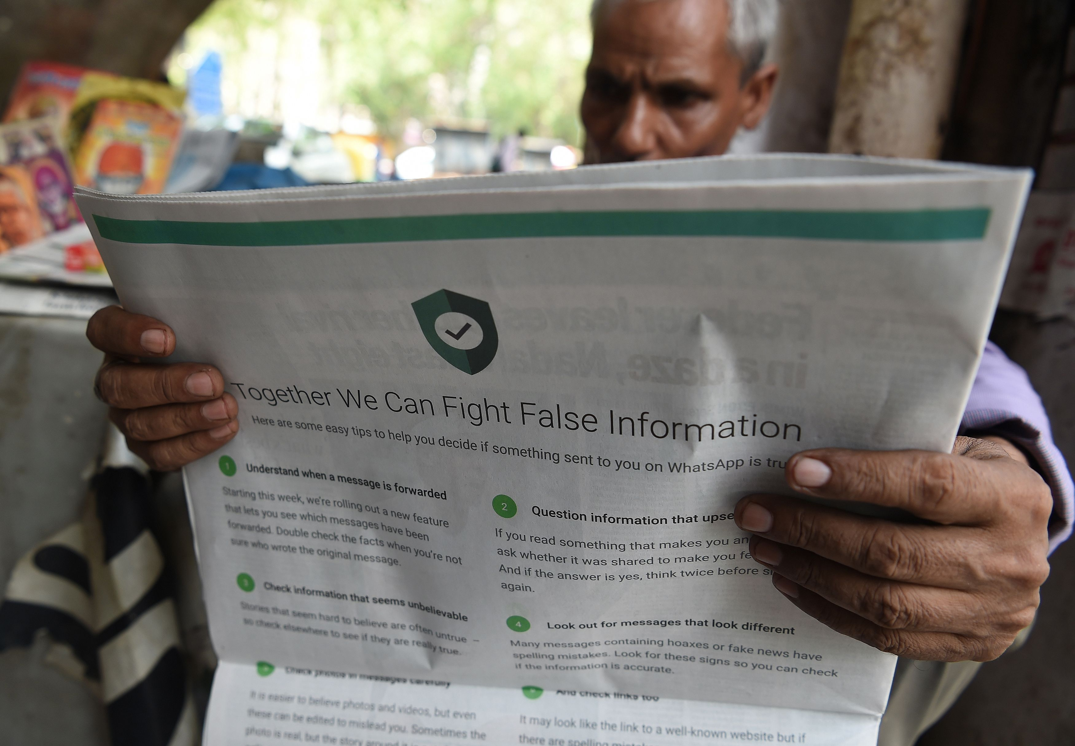 An Indian newspaper vendor reading a newspaper with a full back page advertisement from WhatsApp intended to counter fake information, in New Delhi on July 10, 2018.