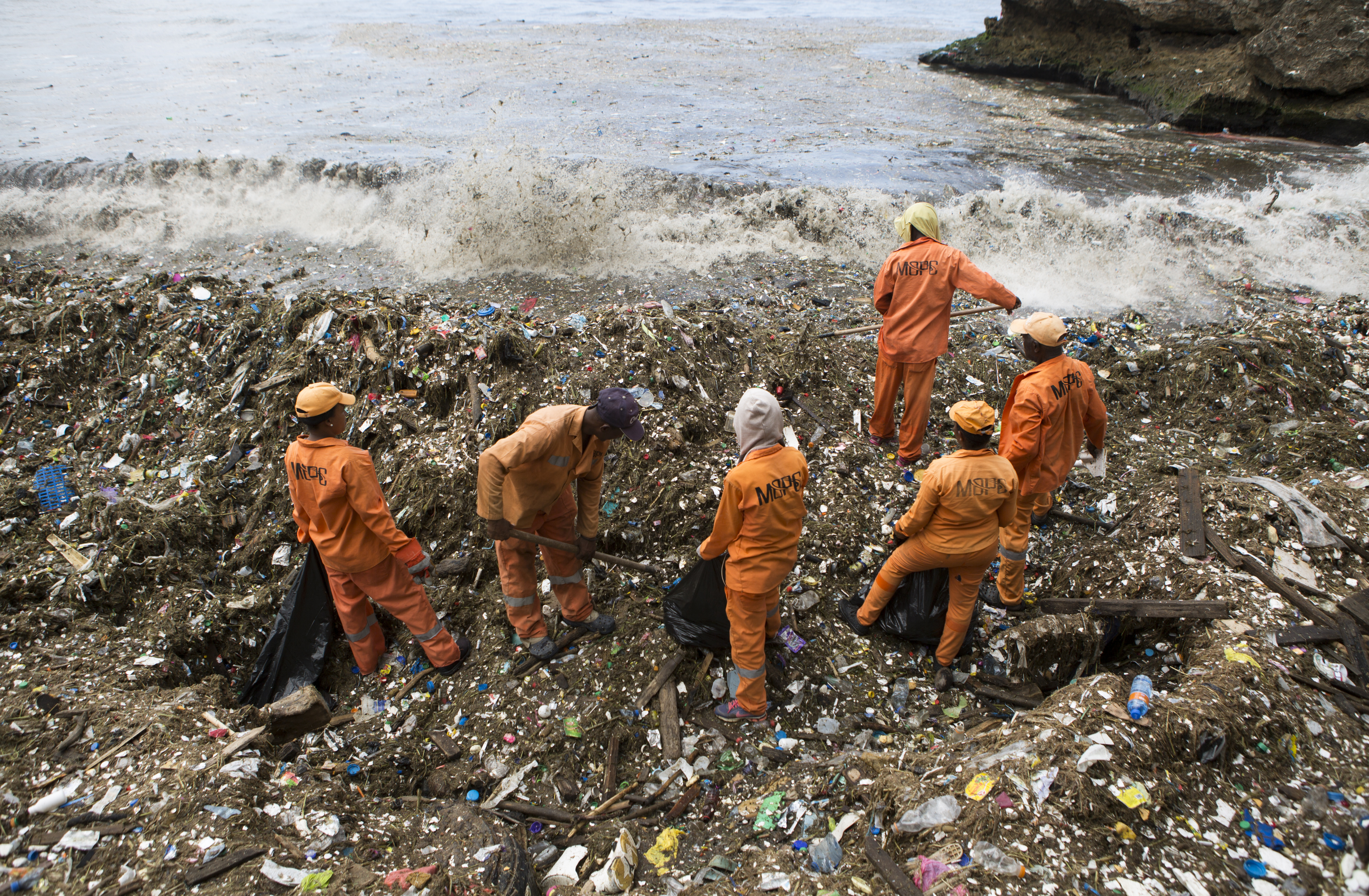 Workers collect rubbish on the coast of Santo Domingo, Dominican Republic, July 16, 2018.