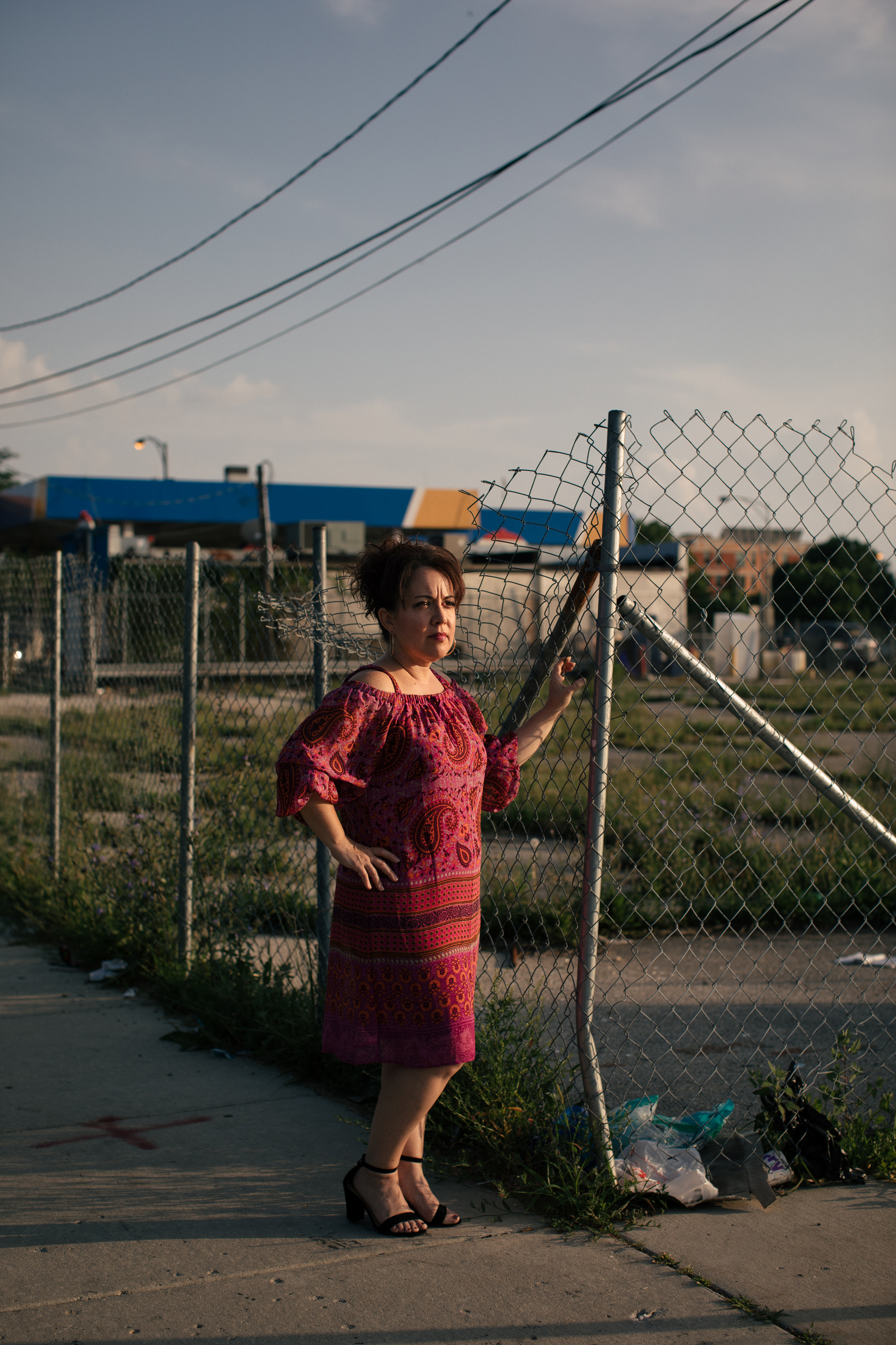 Juanita Irizarry, the Executive Director of Friends of the Parks, poses next to empty lots adjacent to Washington Park on Chicago's South Side. Several lots in the area are empty, and businesses, like the Amstar gas station, could be sold to make way for the Obama Presidential Center.
