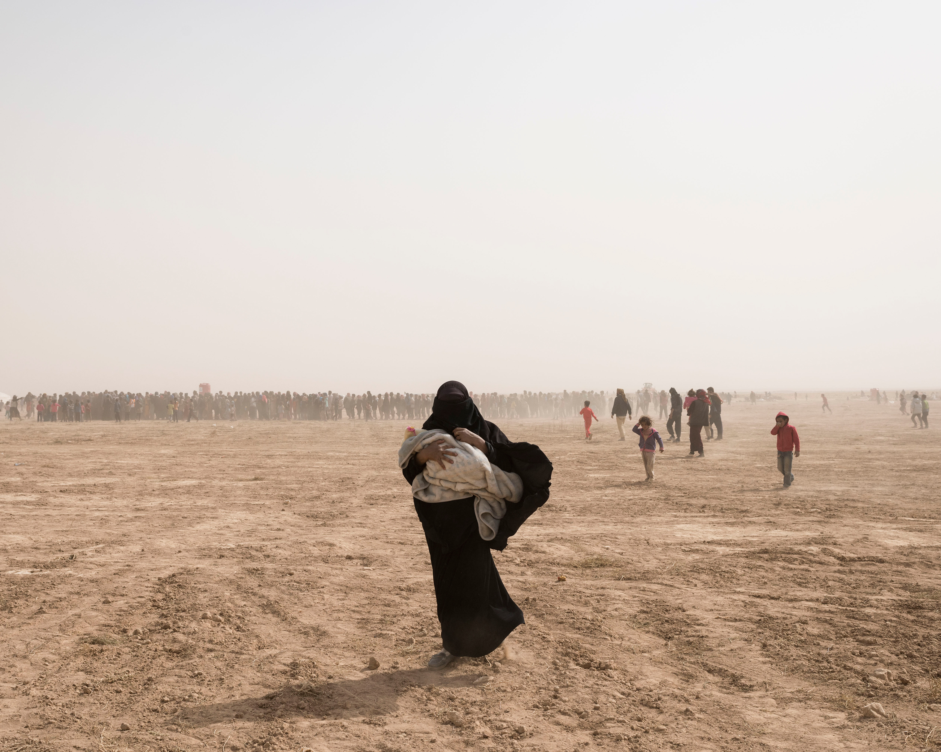 A woman carries her children away from a food-distribution site near Deir ez-Zor, Syria, during a sandstorm in October.