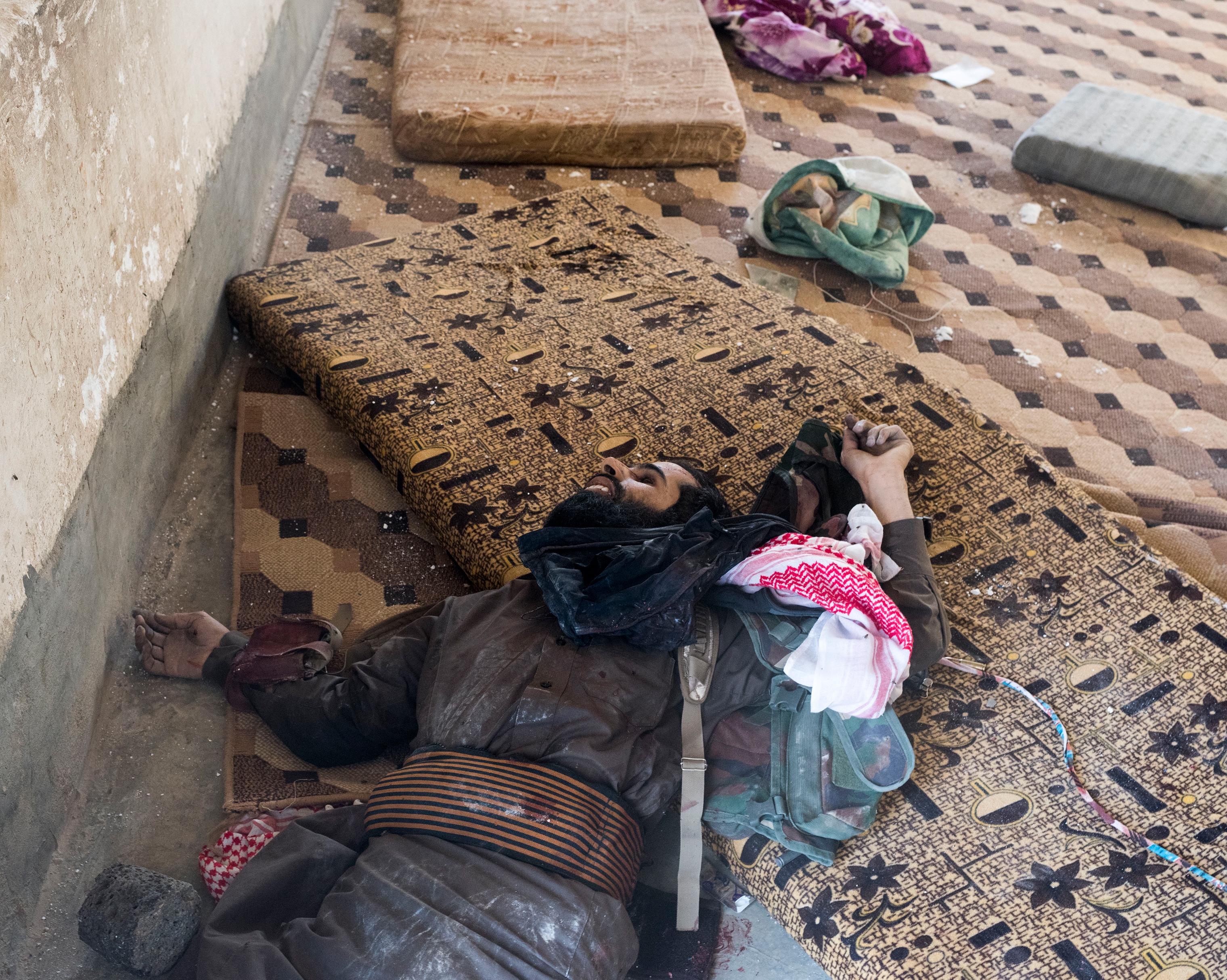 The body of an ISIS fighter killed during fighting with a Kurdish militia on the outskirts of Deir ez-Zor in October. He is still wearing a suicide belt.