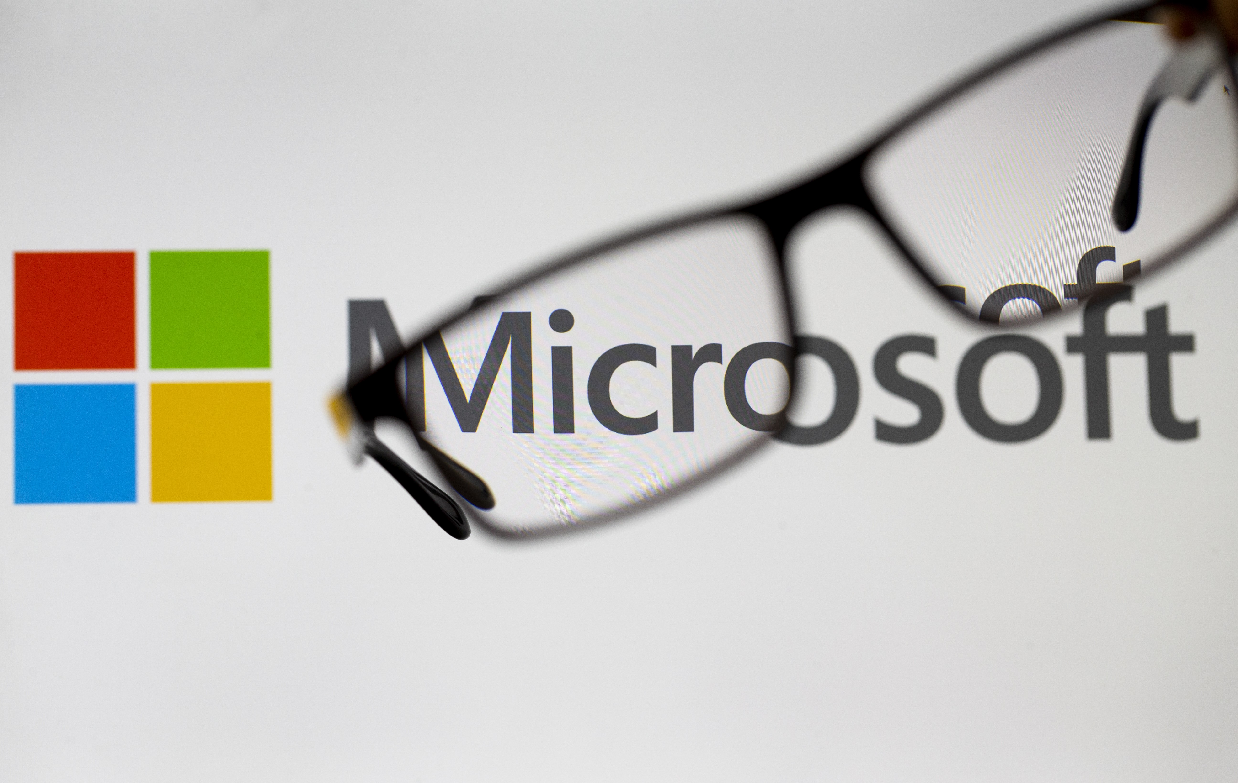 Glasses are seen in front of a computer screen showing a Microsoft logo in Ankara, Turkey on July 19, 2018.