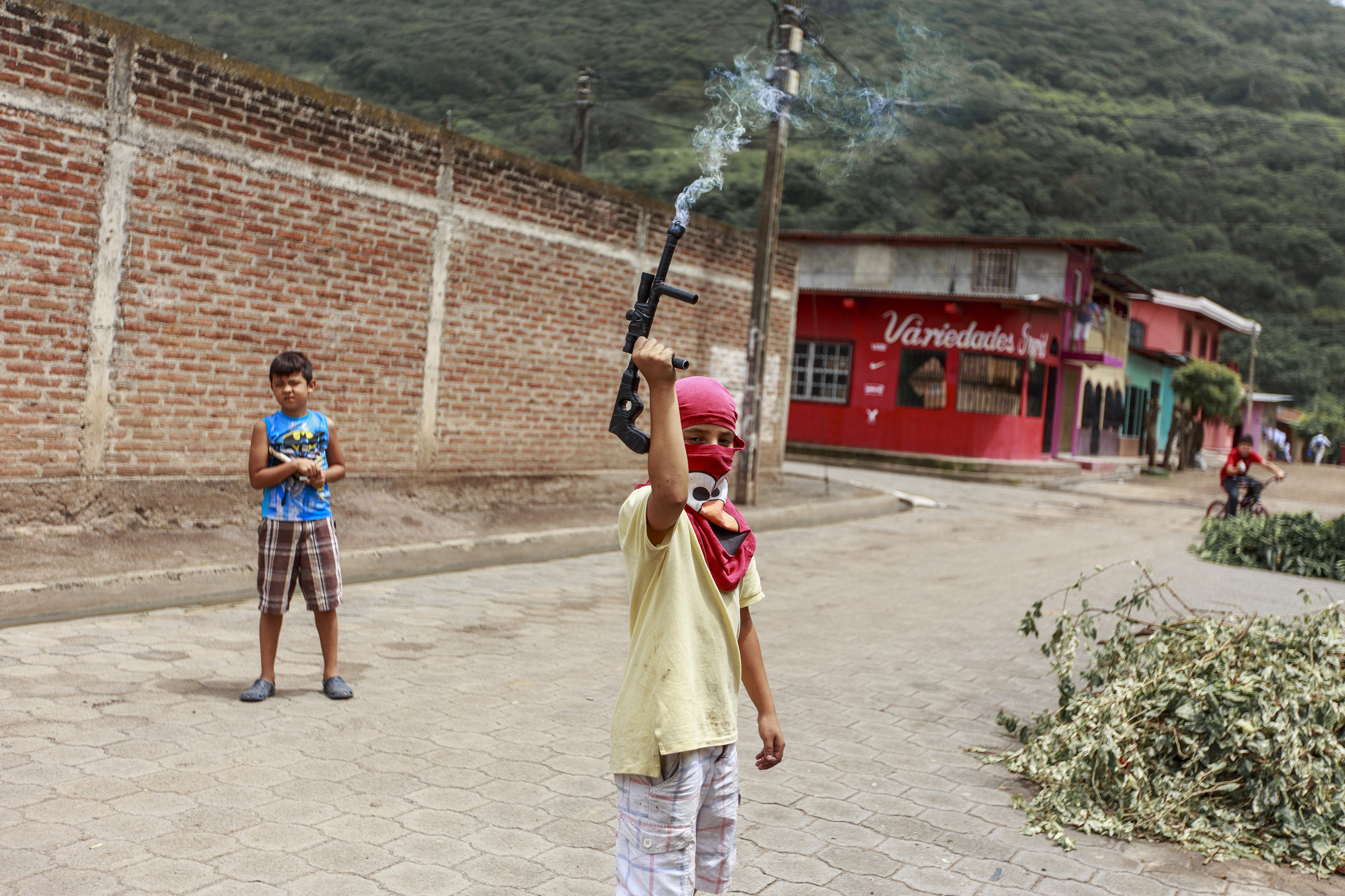 A child with a toy gun—fitted with a firework that emits smoke—pretend to guard a barricade in La Trinidad, a municipality north of Managua, on June 28.