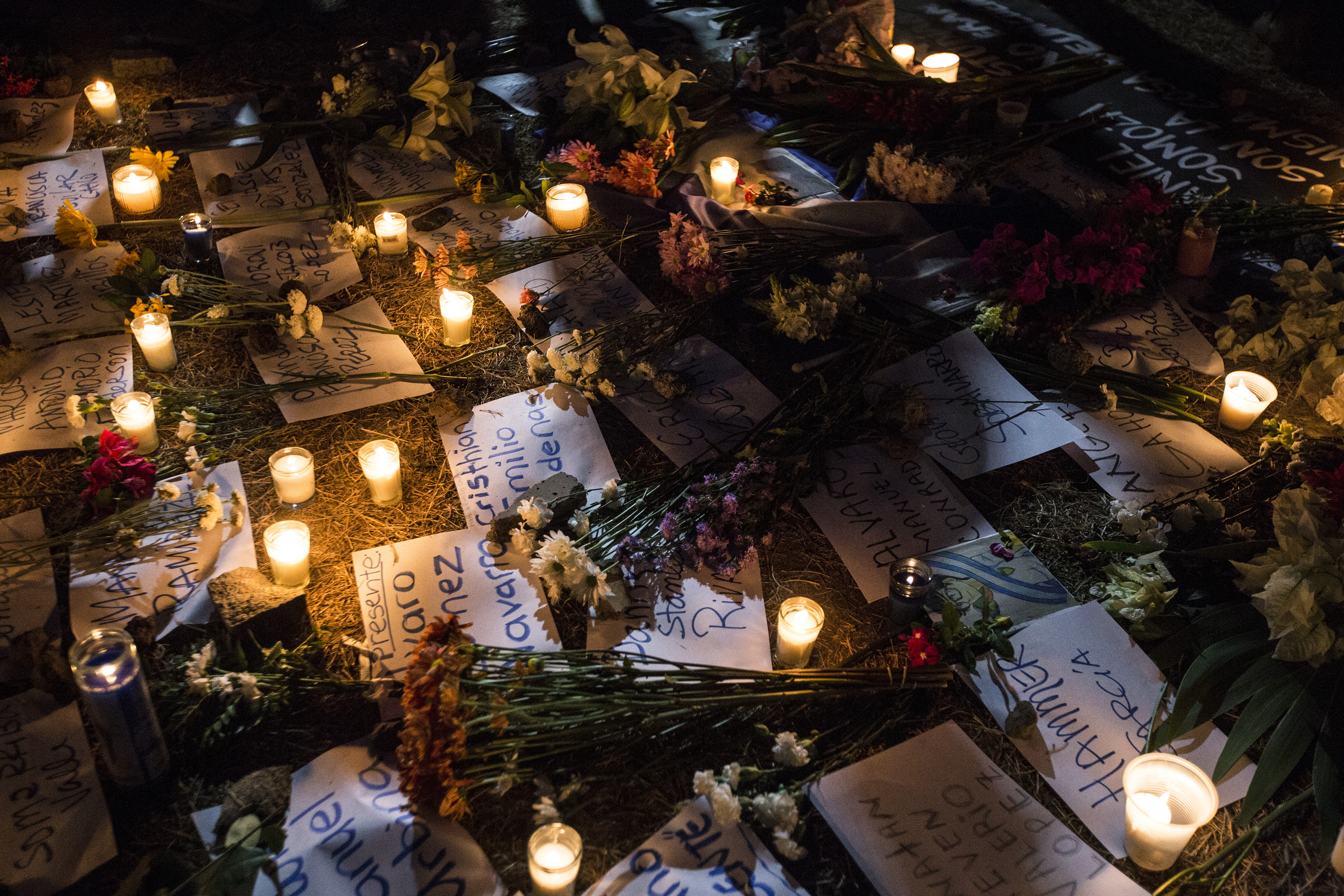 Flowers and candles surround papers written with the names of victims, who were killed during the protests, on April 25.