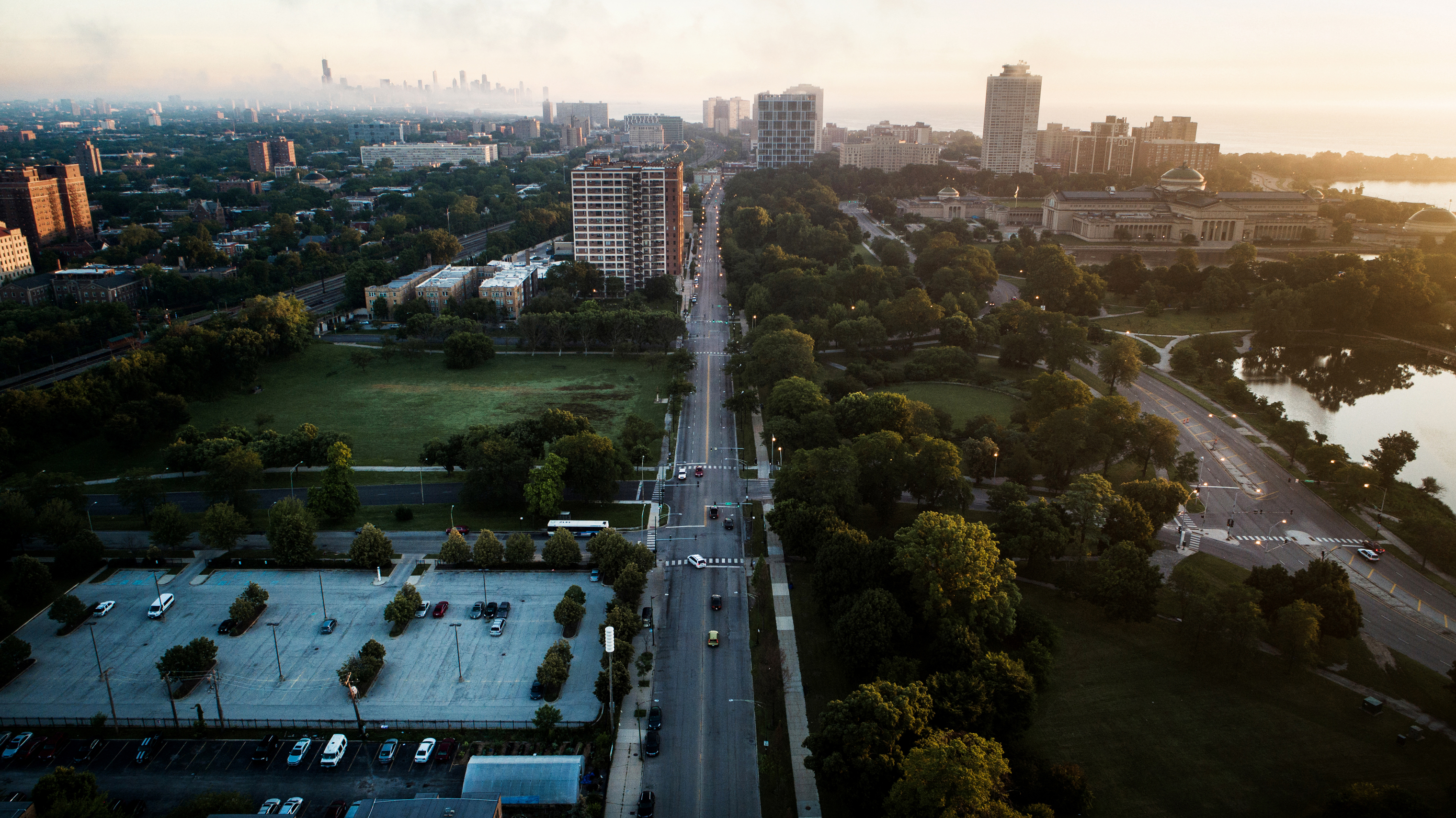The sun rises over apartments in Woodlawn, at left, and Hyde Park, at top, neighborhoods adjacent to Jackson Park. The Obama Presidential Center is currently planned to be built within the green spaces at center and bottom right.