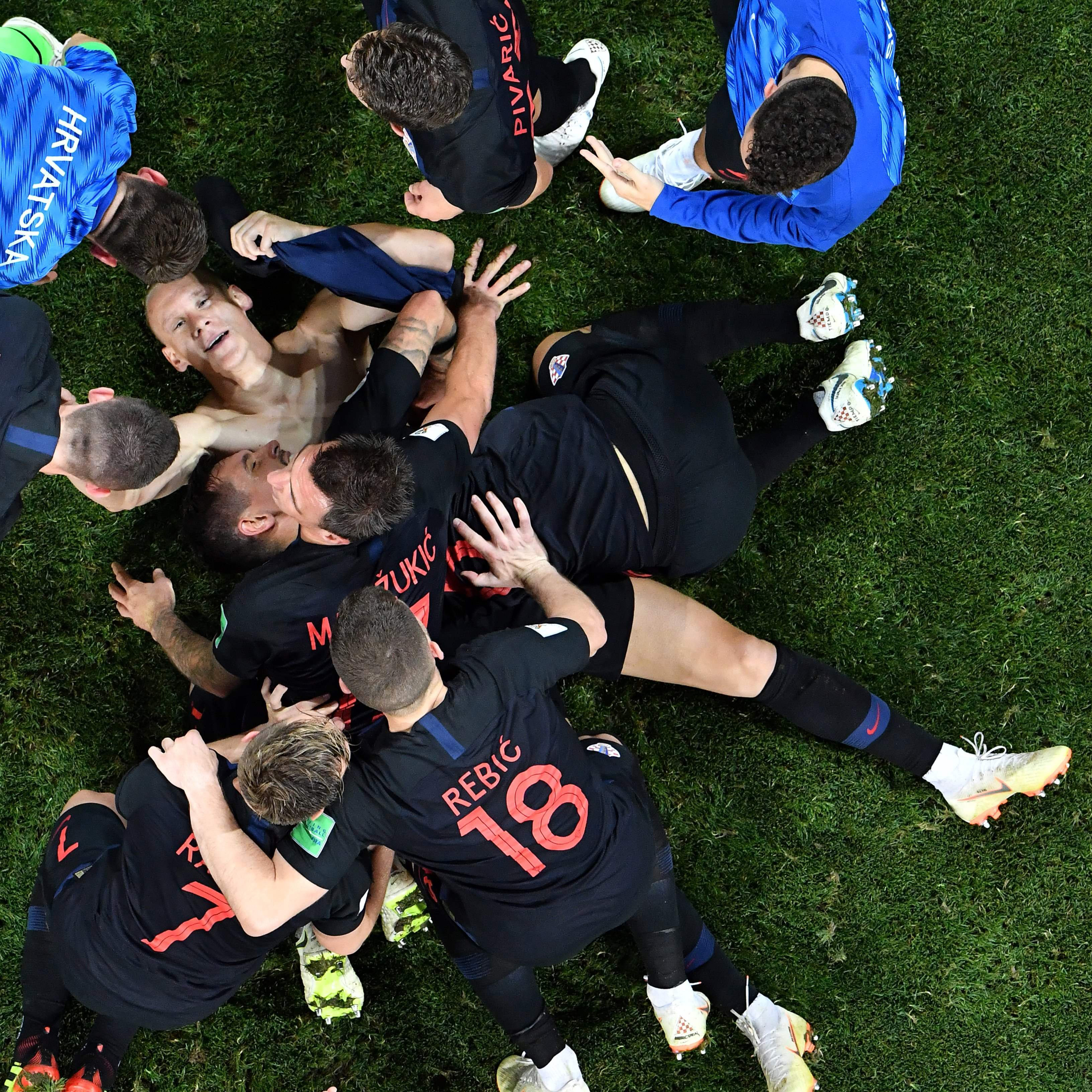 Croatia's defender Domagoj Vida (down) is congratulated by teammates after scoring a goal during the quarter final game between Russia and Croatia on July 7, 2018.