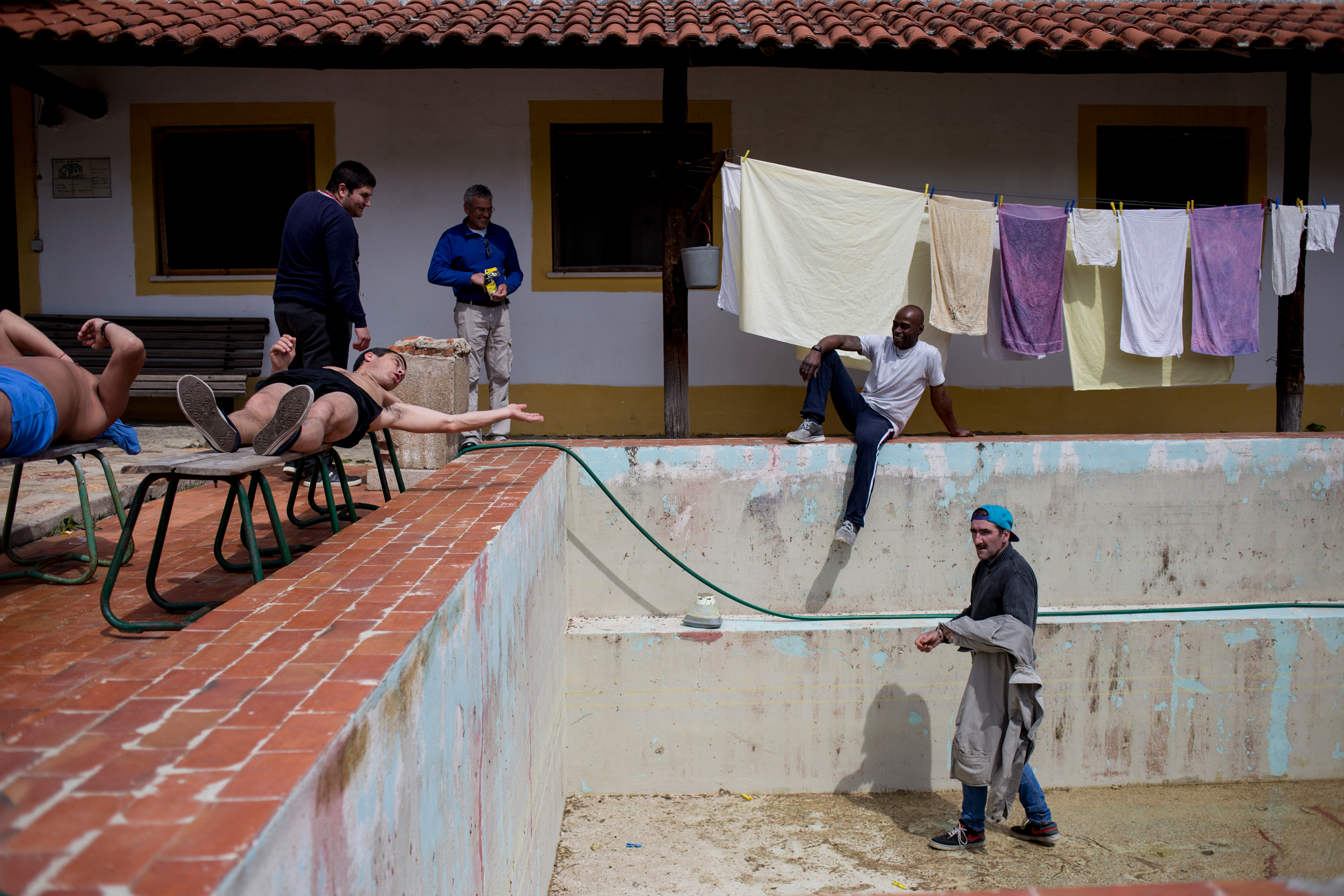 Carlos (right), steps into the swimming pool, which is being renovated, while other patients at Ares do Pinhal Therapeutic Community look on, March 30, 2017.