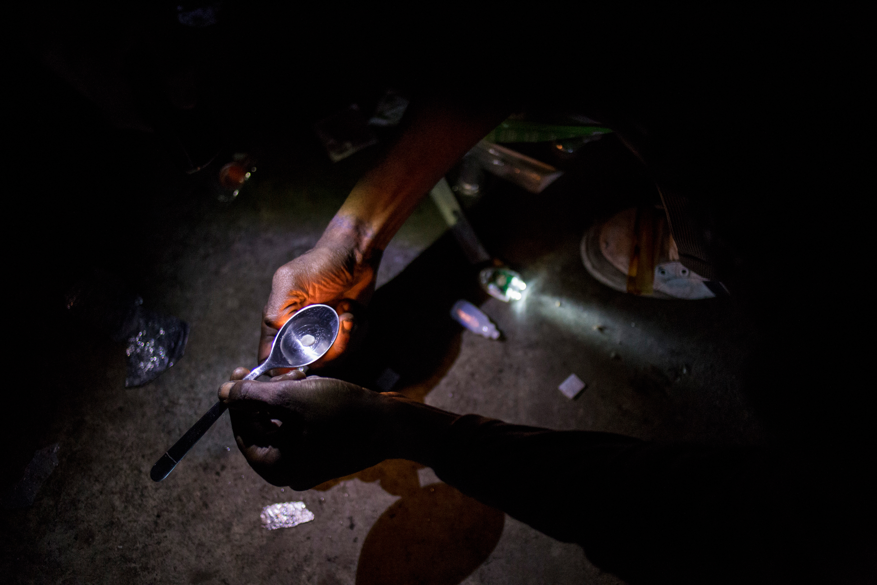 A man prepares a hit of cocaine with the kit provided by the outreach team, in Lamin's room, near Casal Ventoso, in Lisbon, February 6, 2017.