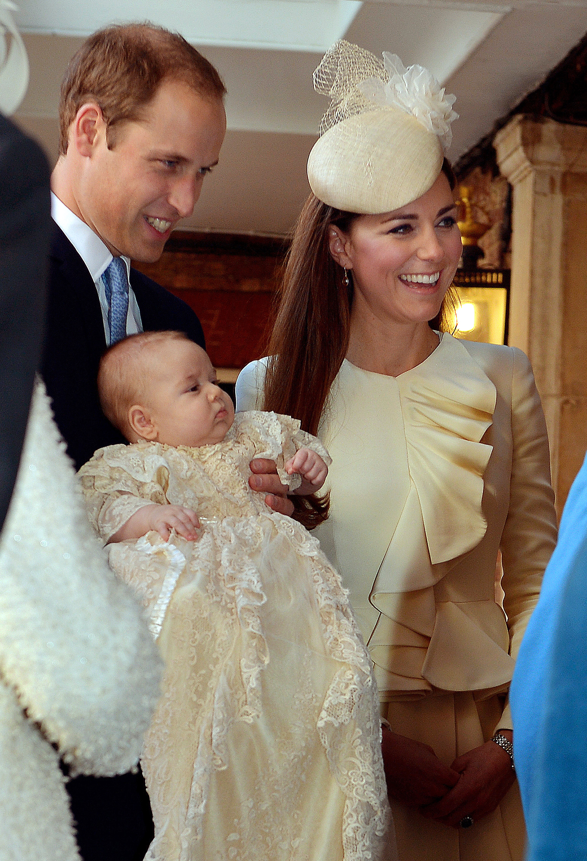 The Duke of Cambridge and his wife Catherine, Duchess of Cambridge, arrive with their son Prince George at Chapel Royal in St James's Palace in central London on October 23, 2013, ahead of the christening of the three month-old prince.