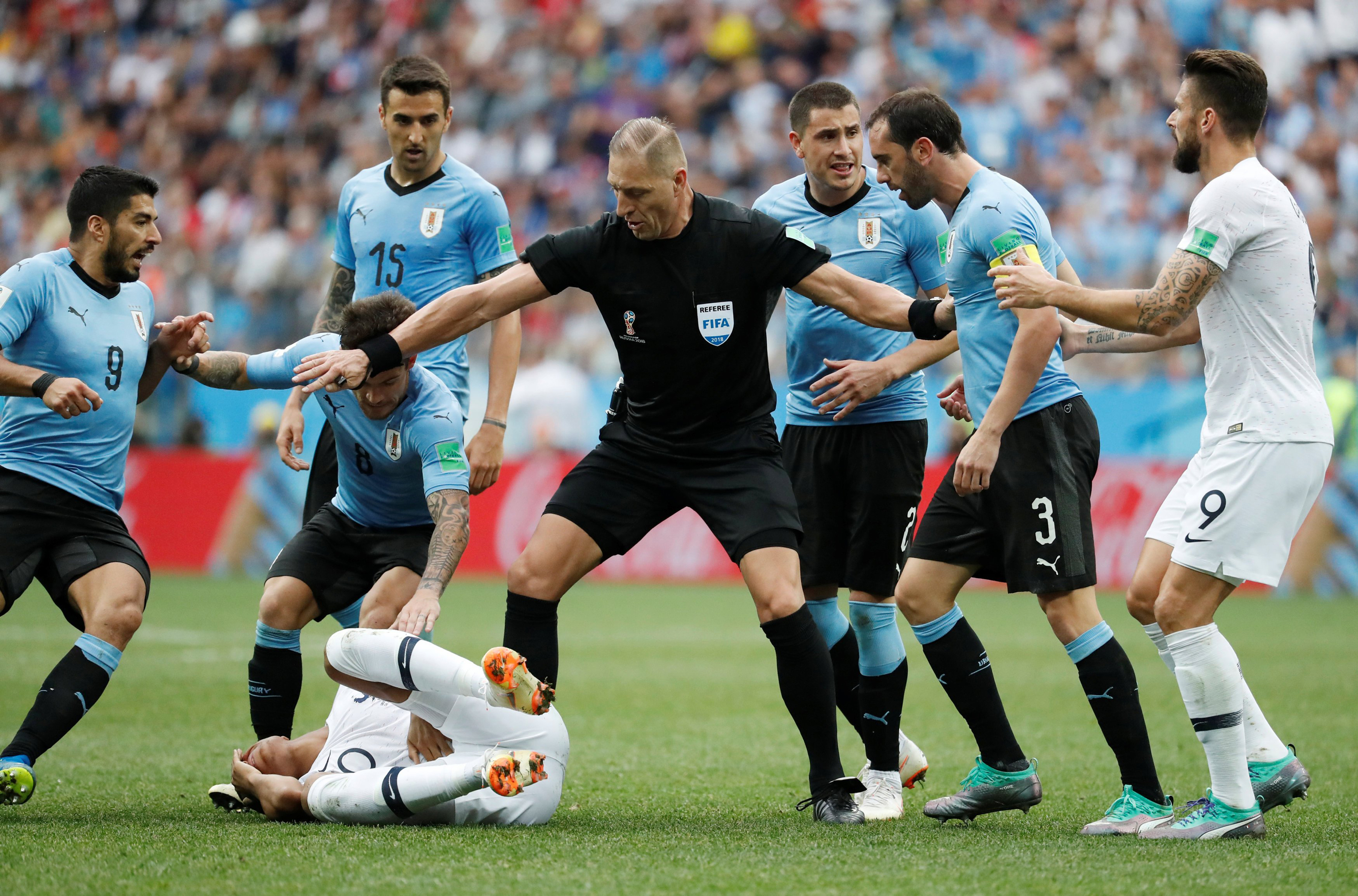 Referee Nestor Pitana intervenes with Uruguay's Diego Godin after clashing with France's Kylian Mbappe on July 6, 2018.