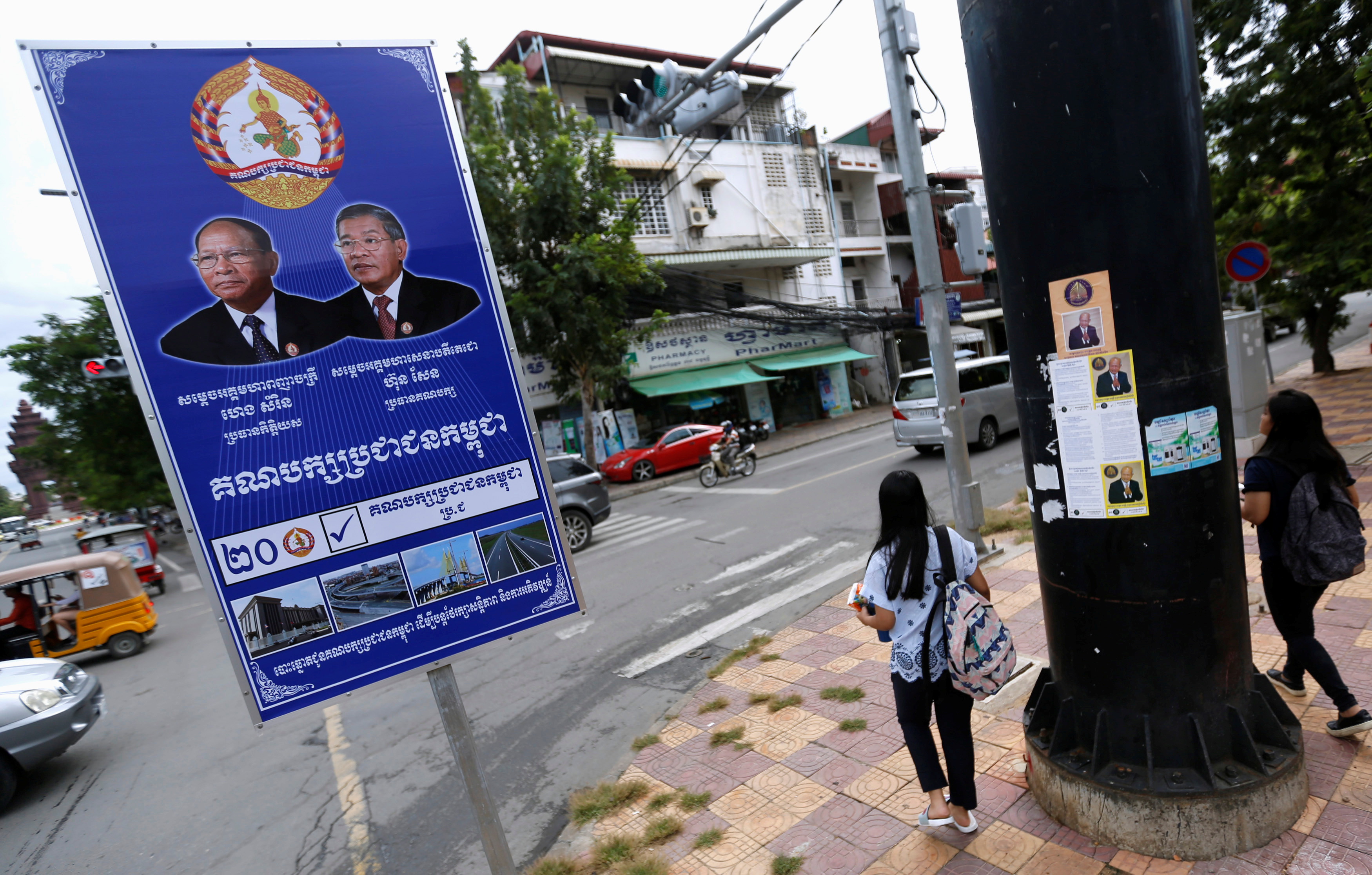 Girls walk by campaign posters for the Cambodian People's Party (CPP) in Phnom Penh, Cambodia on July 17, 2018.