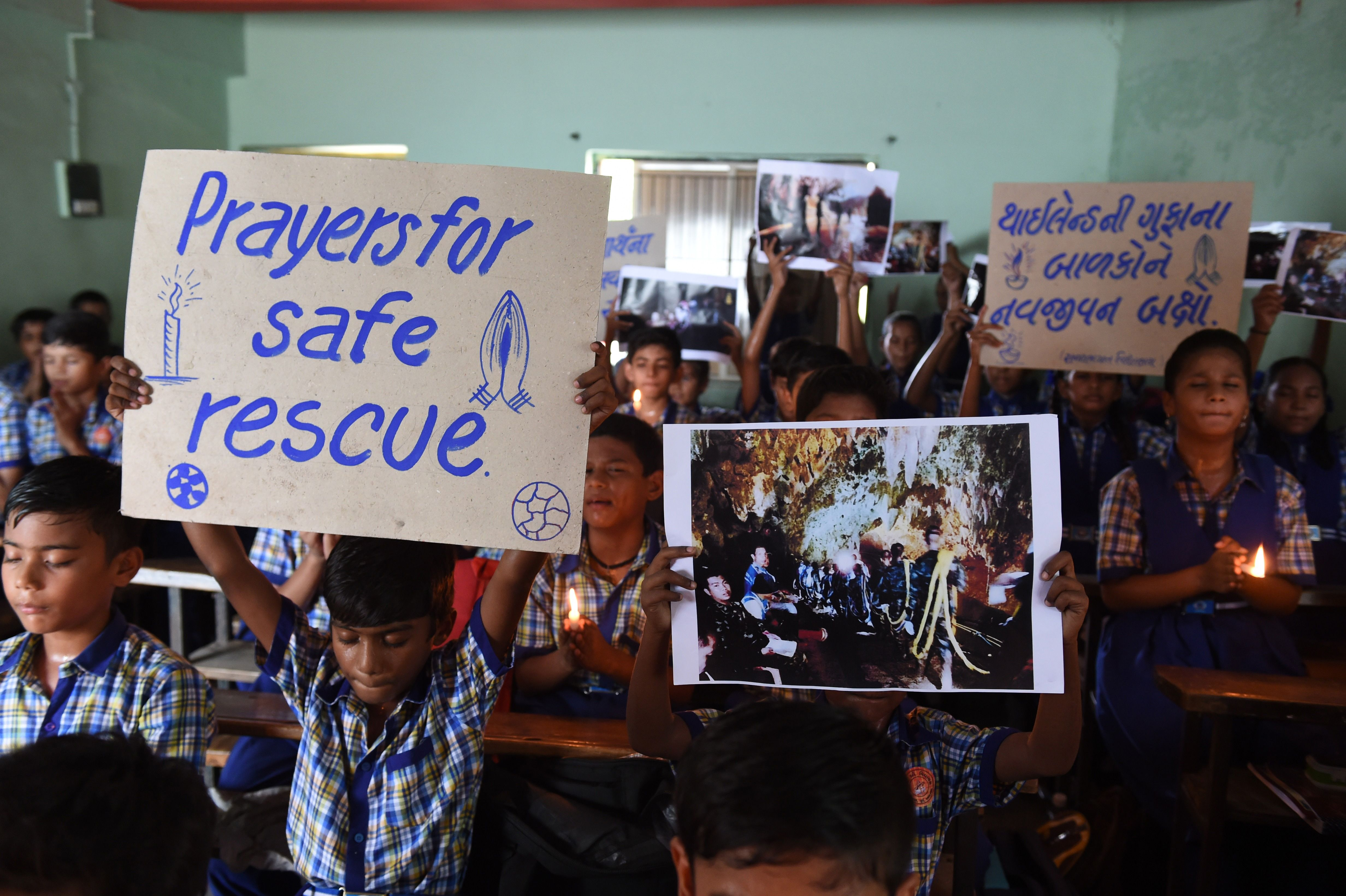 Indian schoolchildren hold placards and pictures during a prayer event for the safe rescue of young football players and their coach stuck in a cave in Thailand, in Ahmedabad on July 9, 2018.