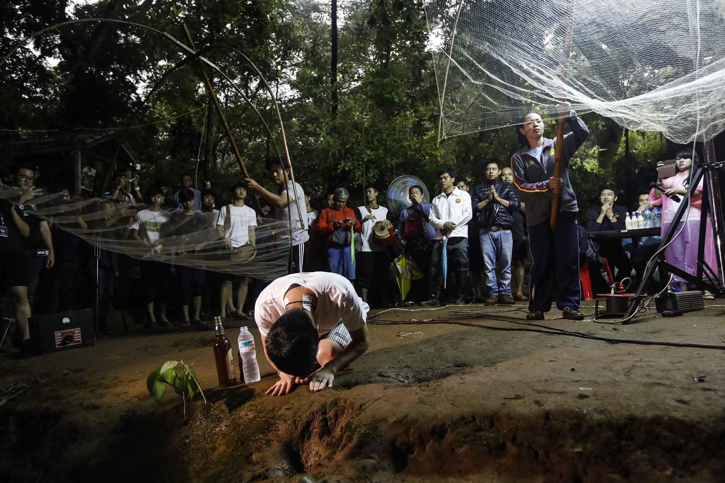 Family members and relatives pray at the entrance of Tham Luang cave while rescue personnel conduct operations to find the missing members of the children's football team along with their coach at the cave in Khun Nam Nang Non Forest Park in Chiang Rai province on June 26, 2018.