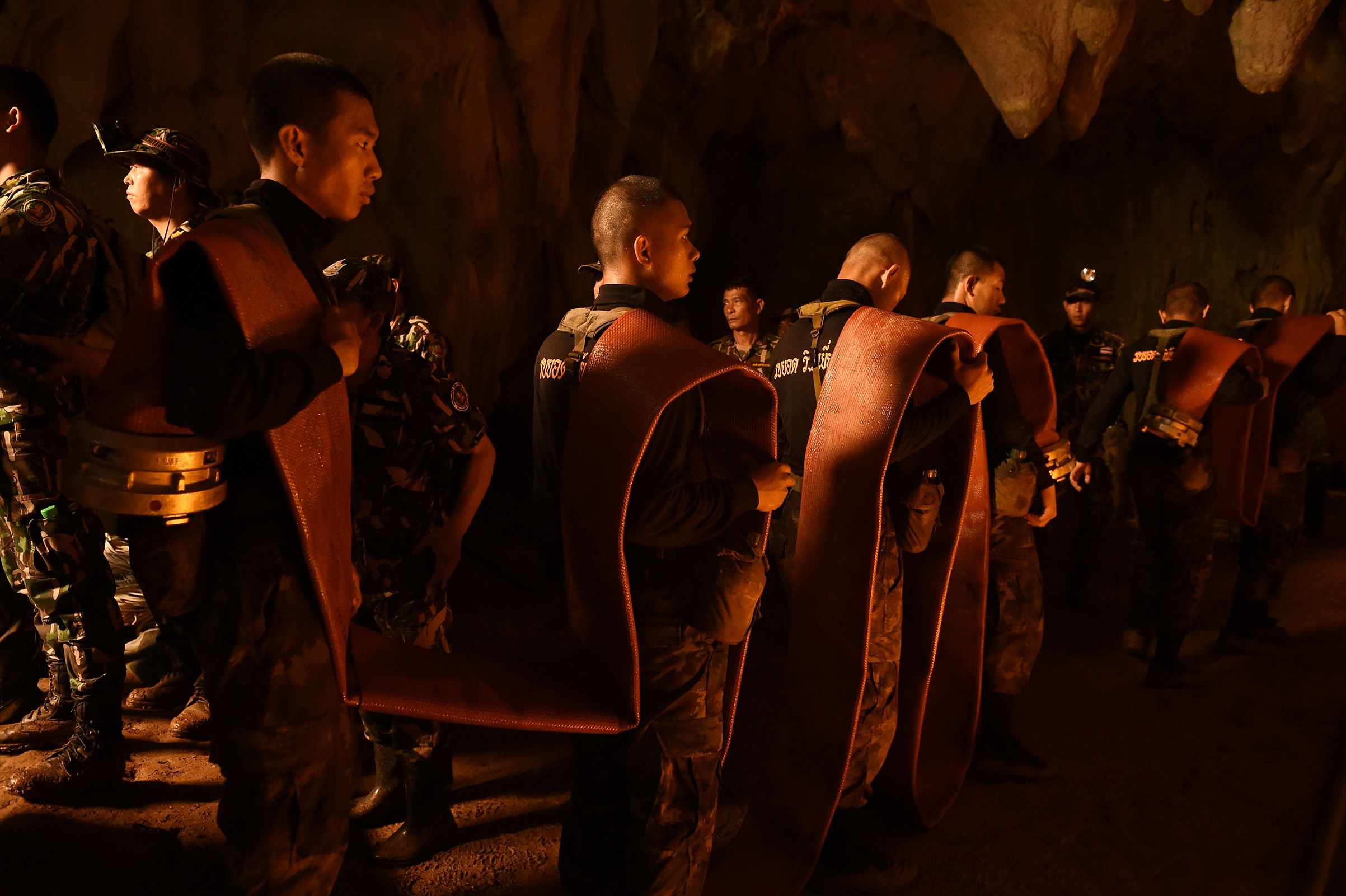 Thai soldiers carry hose deep into the Tham Luang cave to pump out water at the Khun Nam Nang Non Forest Park in Chiang Rai on June 27, 2018 during a rescue operation for a missing children's football team and their coach.