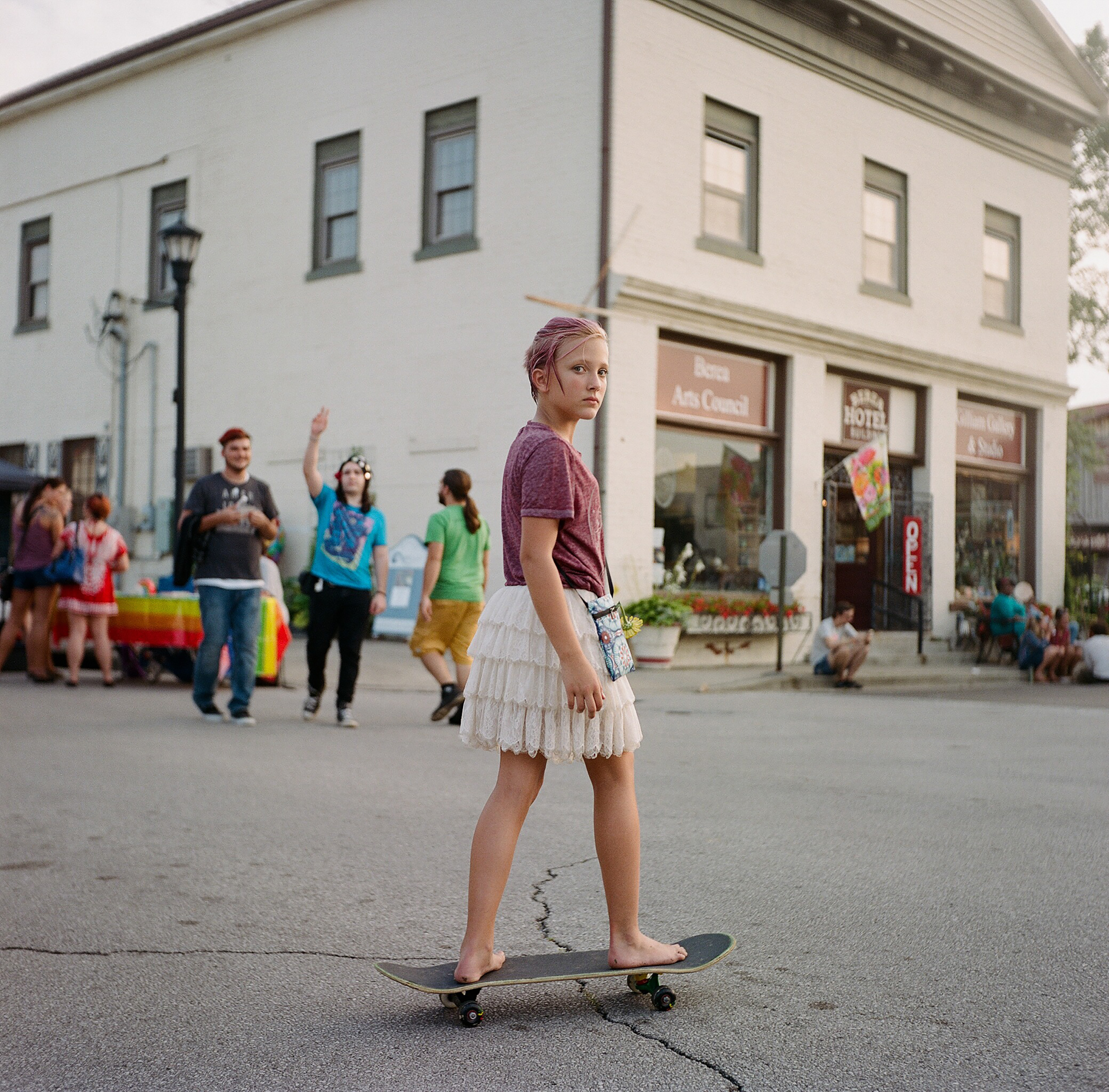 A young woman skates in front of an LGBT Pride booth at a music festival in Berea, KY