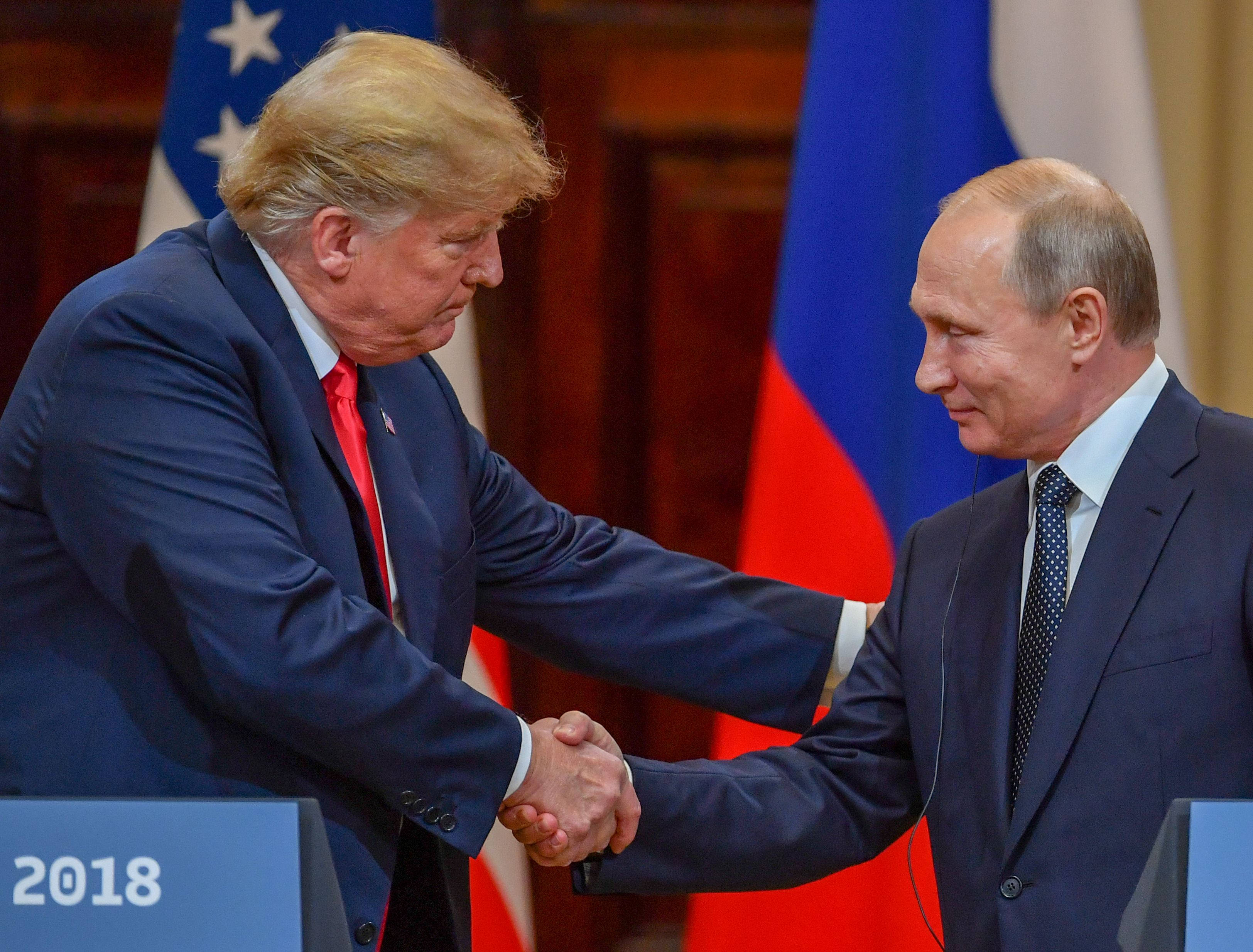 JULY 16 - US President Donald Trump  and Russia's President Vladimir Putin shake hands before attending a joint press conference after a meeting at the Presidential Palace in Helsinki.