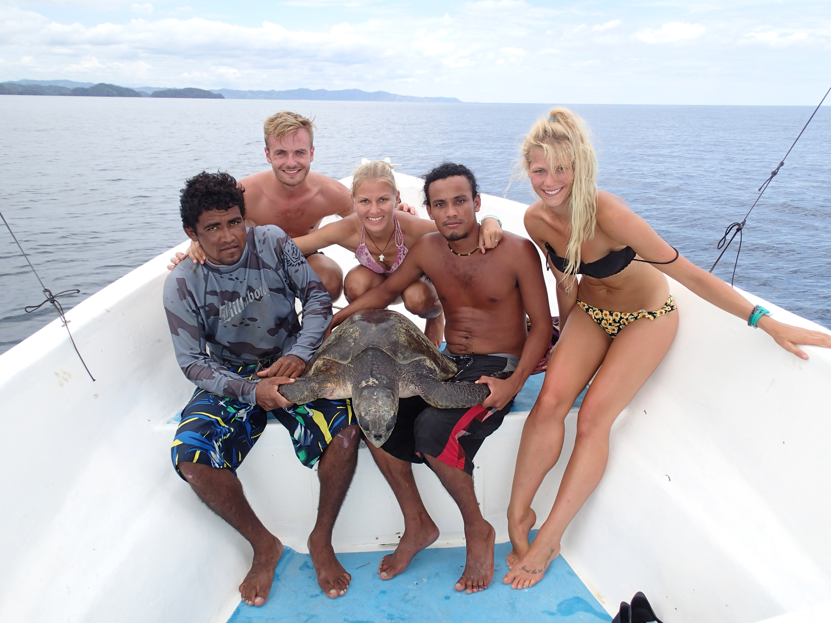 Figgener poses with a sea turtle and members of her research team on their boat in Costa Rica in 2015. L to R: Macdonal Gomez, Daniel Stuart, Christine Figgener, Andrey MacCarthy, and Vee Koleff.